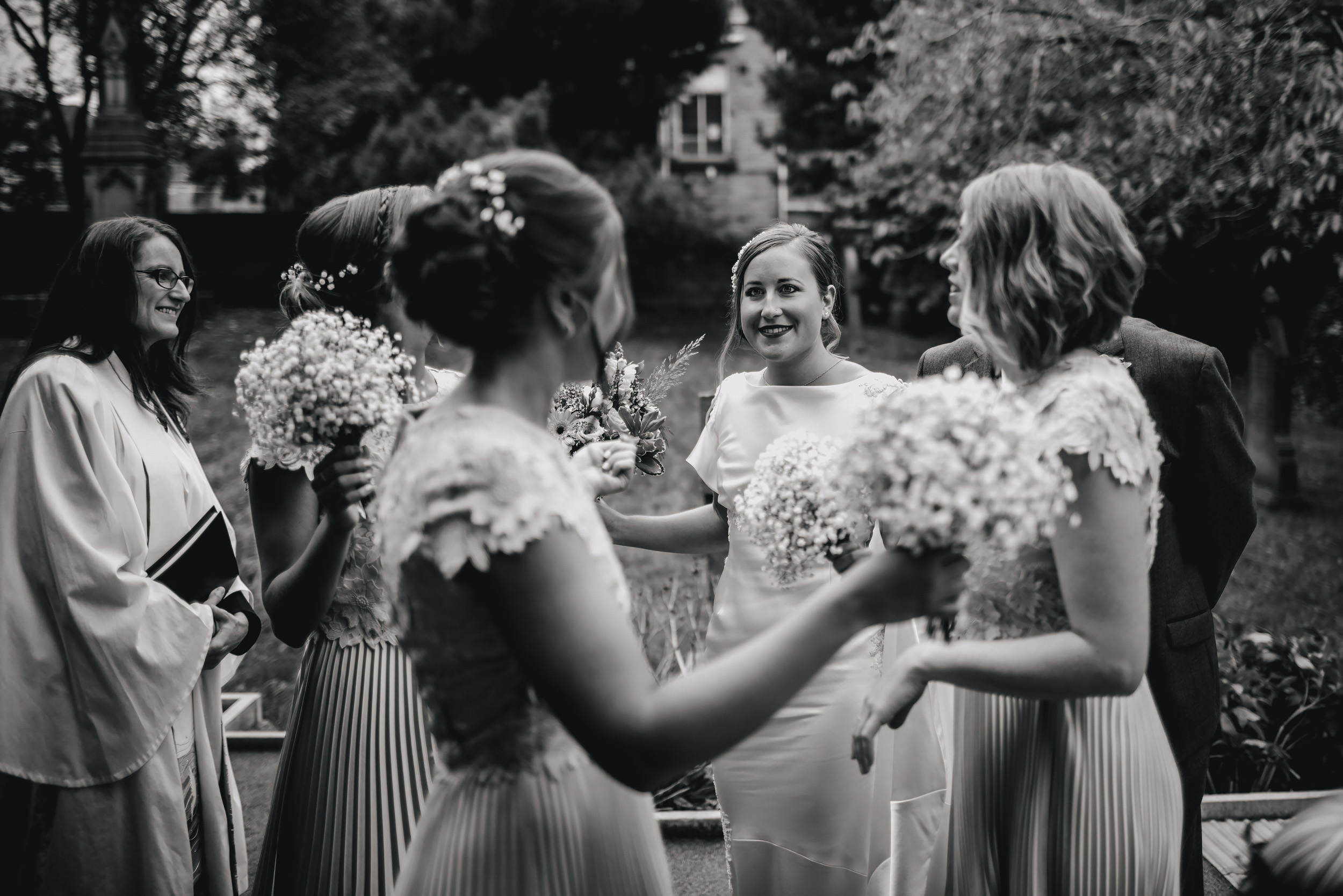 Bride and bridesmaids waiting in the church gardens