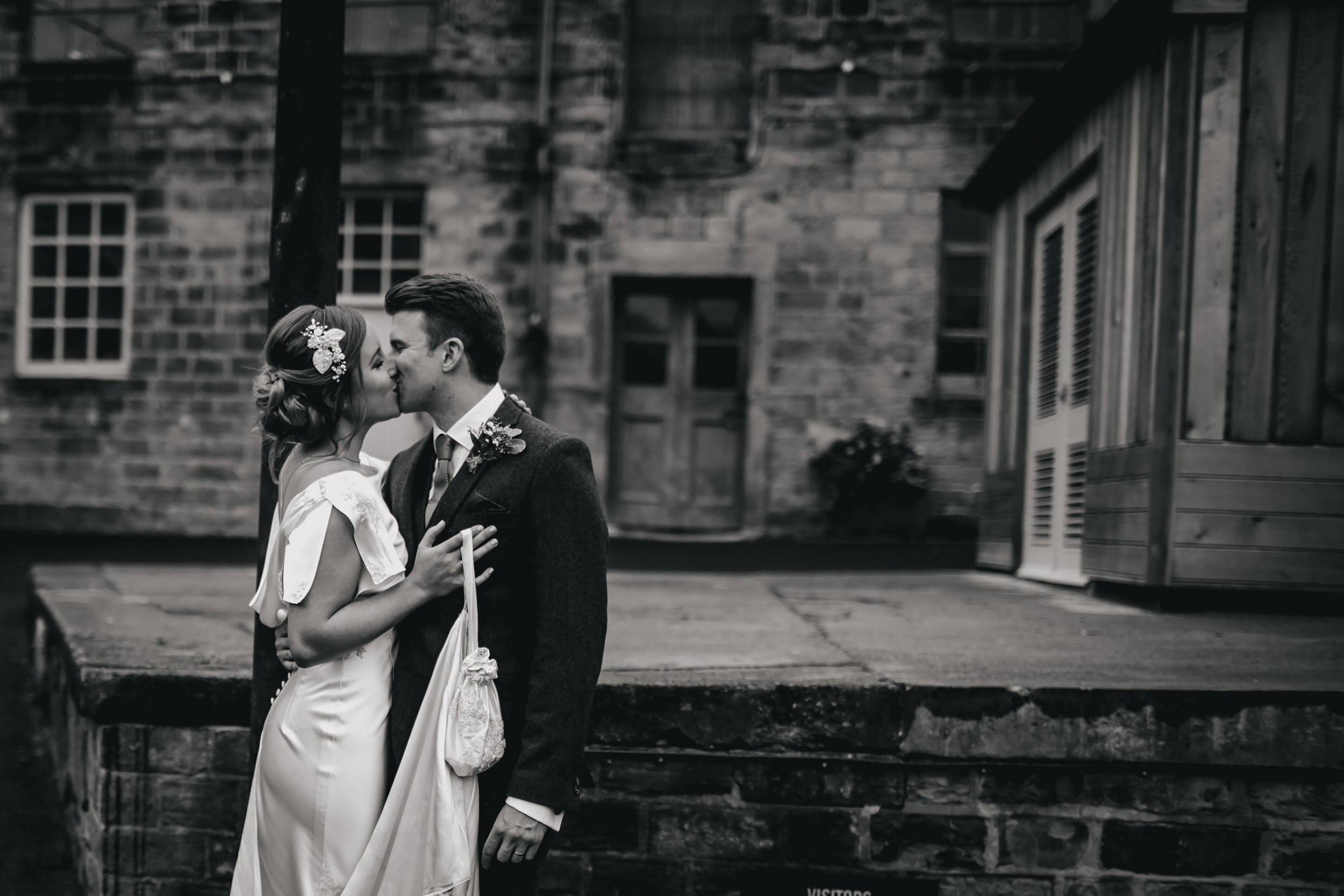 Bride and groom share a kiss at Sunny Bank Mills