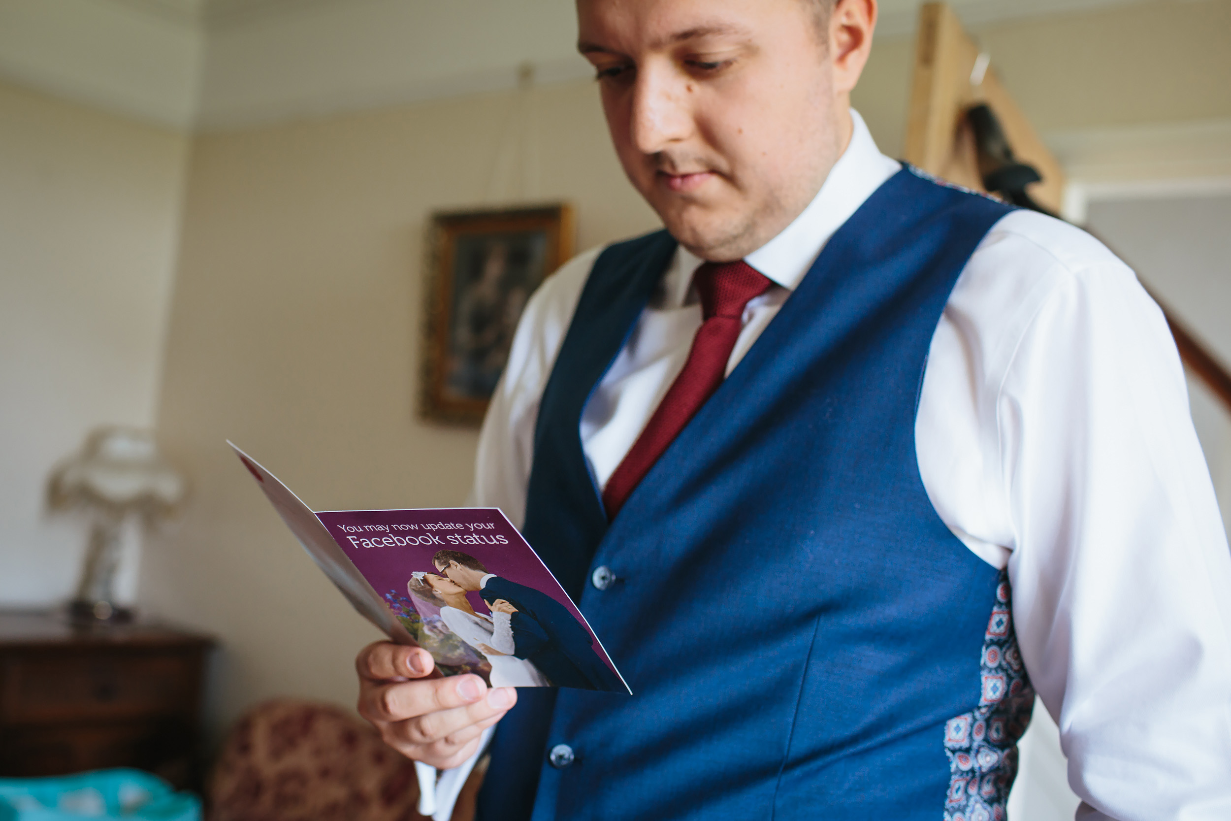 Groom reads a card before his wedding in Lancashire