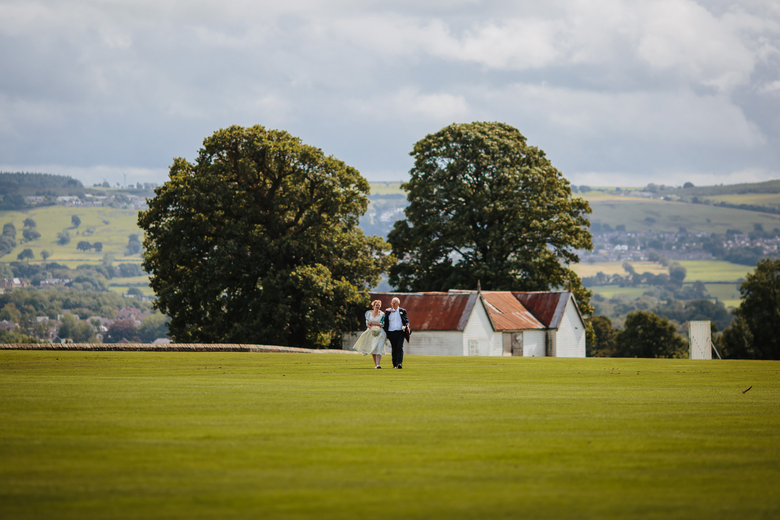 Bride and her father walk towards her wedding in Lancashire