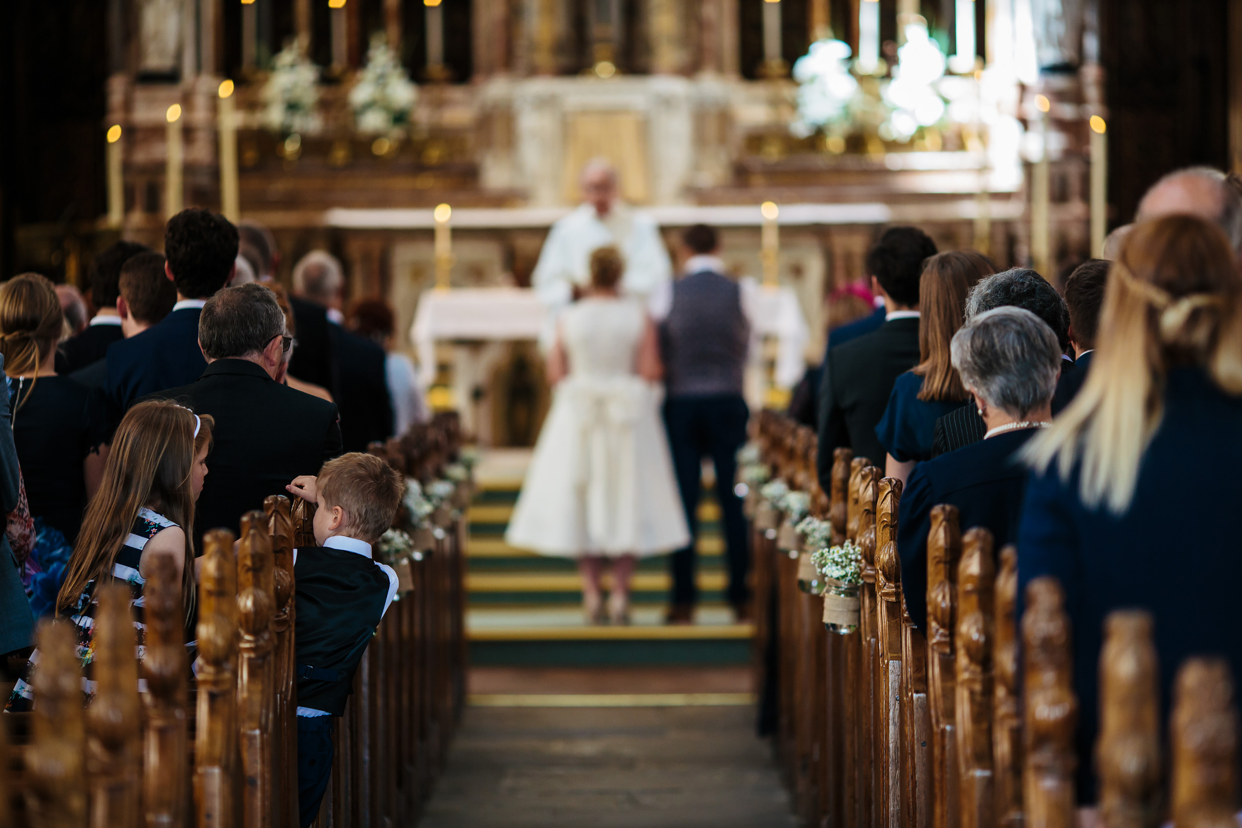 Young boy in the church pews at a wedding in Lancashire