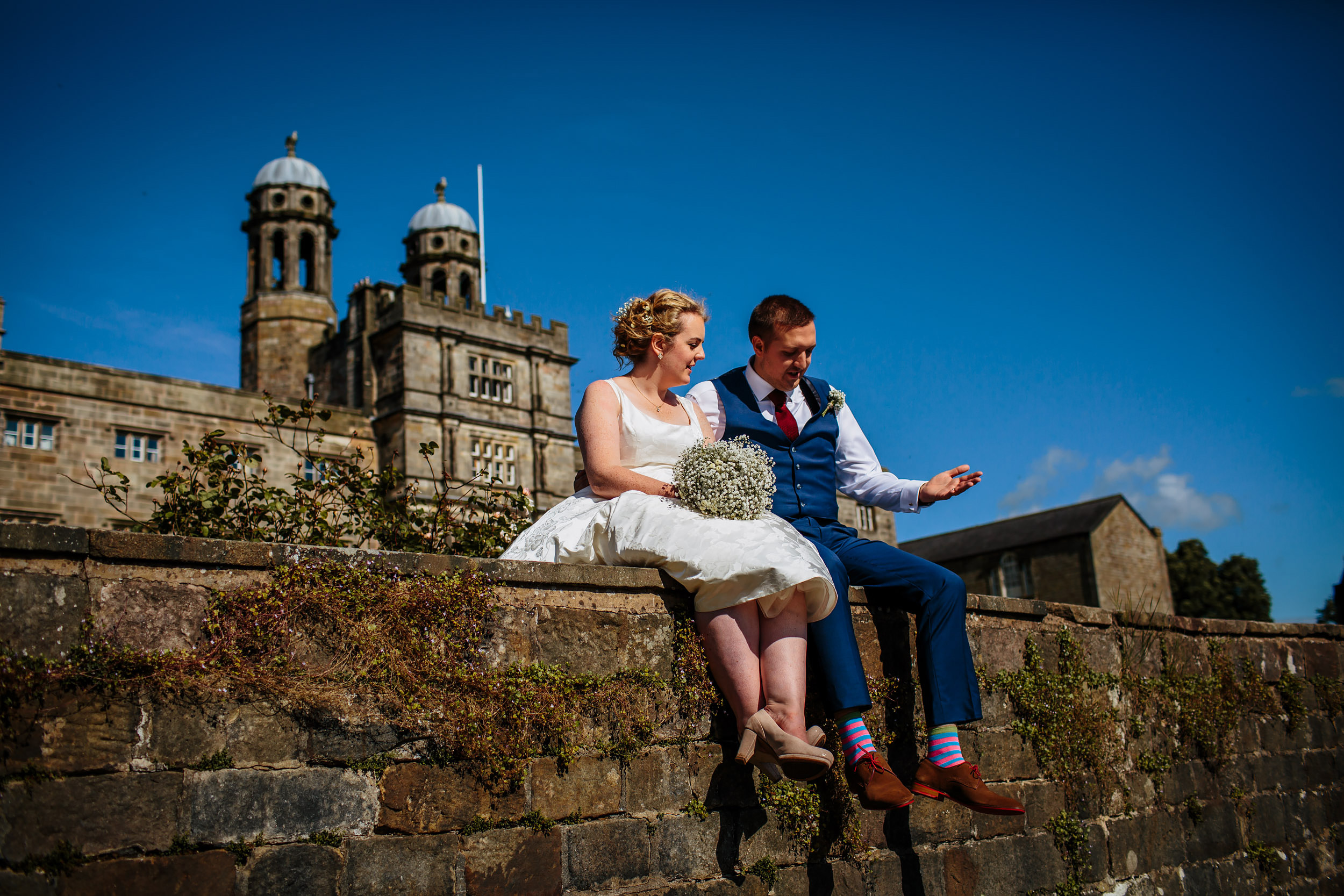 Bride and groom sitting on a wall at Stonyhurst College