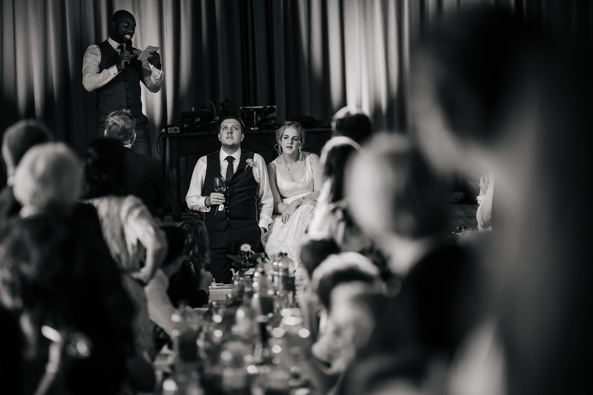 Bride and groom listening to the speeches on their wedding day