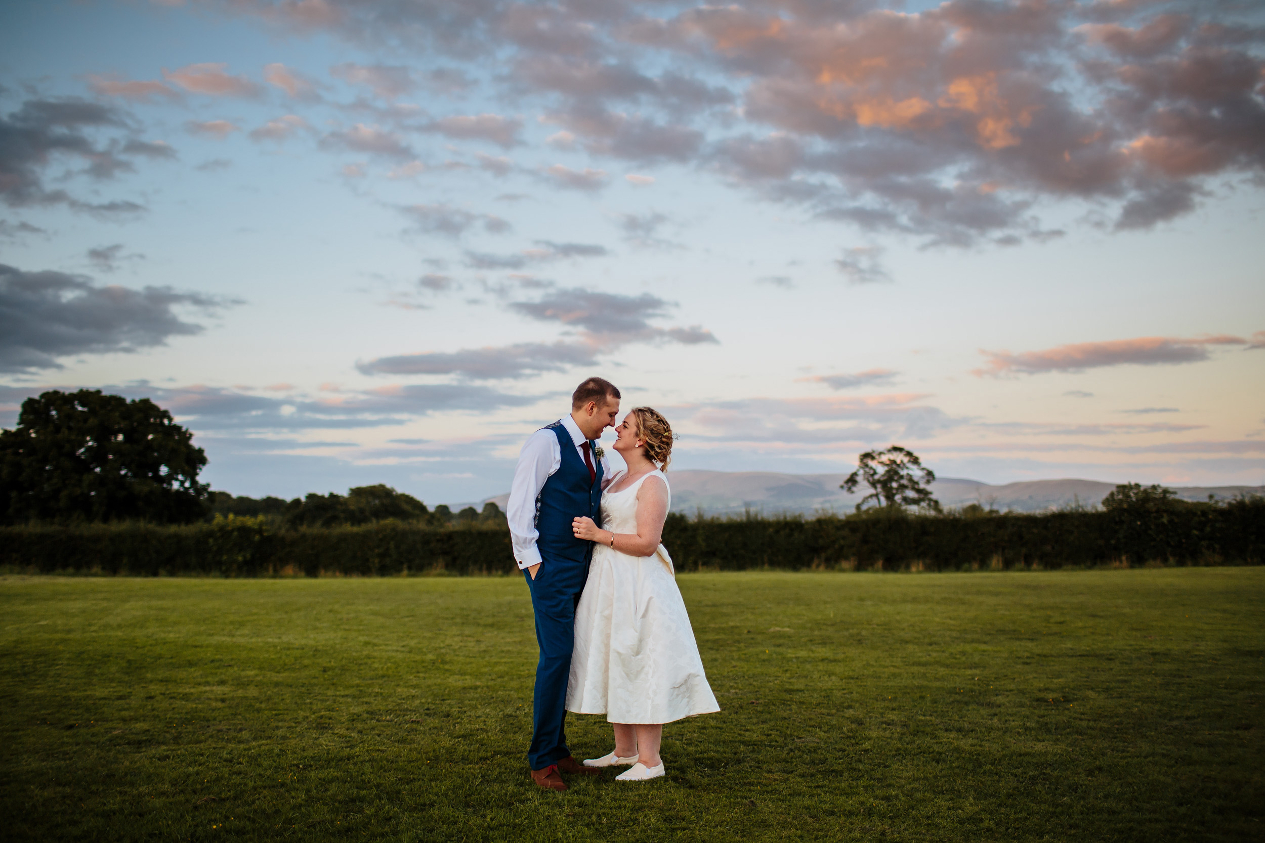 Bride and groom pose for a photograph on their wedding day in Lancashire