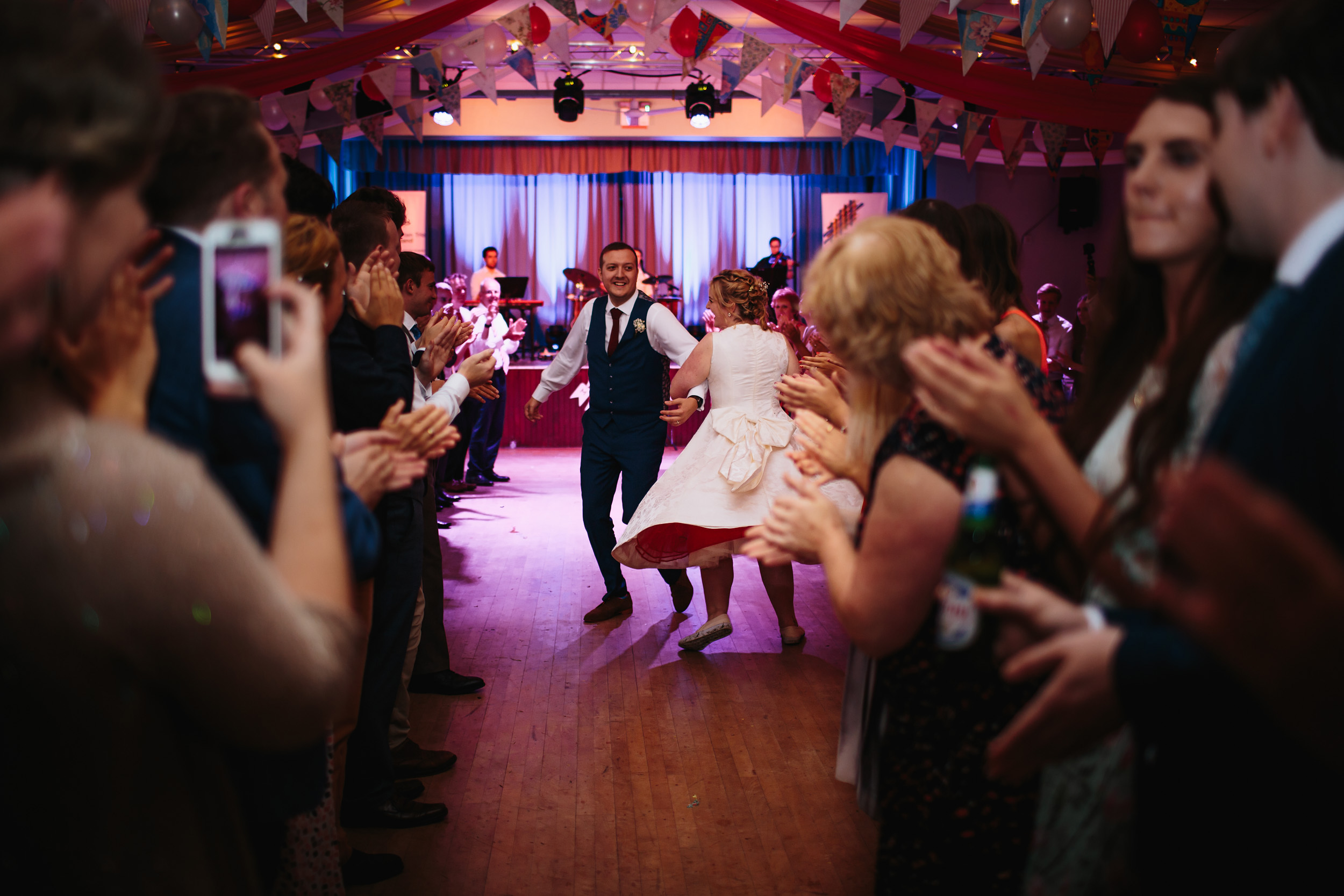 Bride and groom ceilidh dancing at their wedding in Lancashire