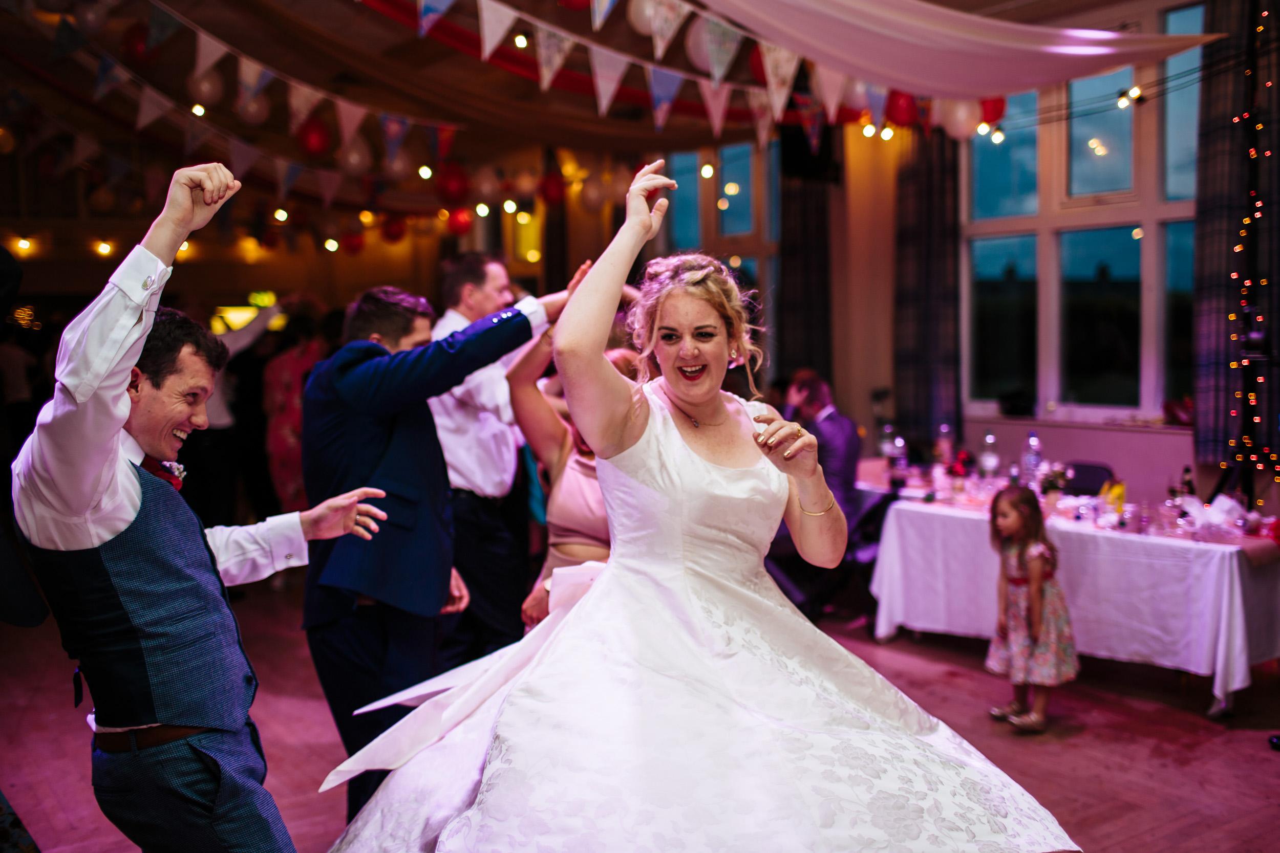Bride ceilidh dancing at her wedding