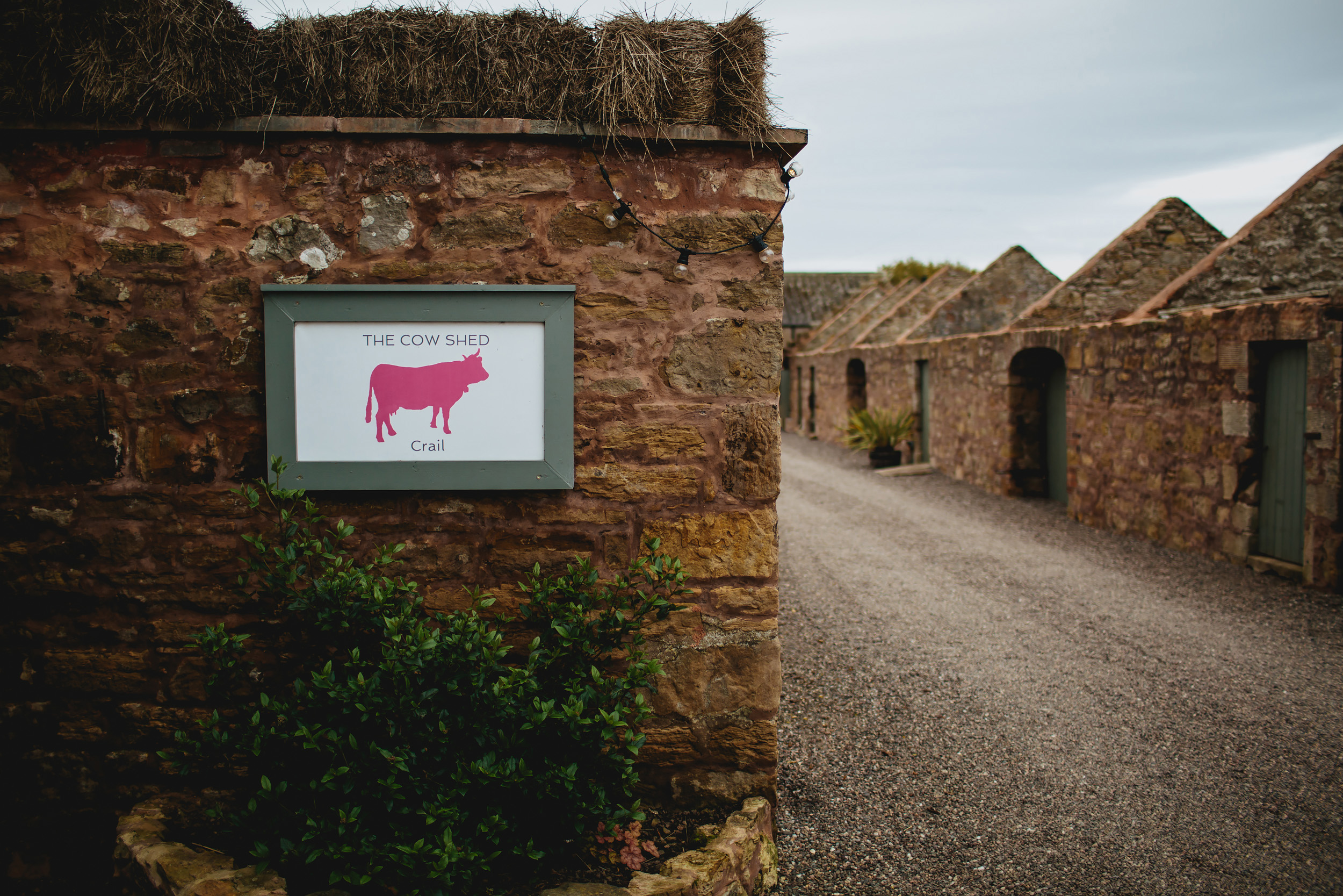 External brick wall and sign at Cow Shed Crail