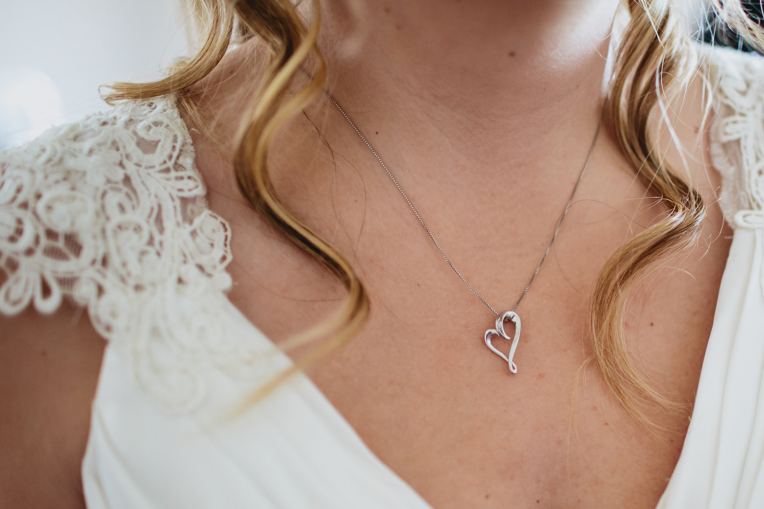 Close up of the bride wearing her necklace