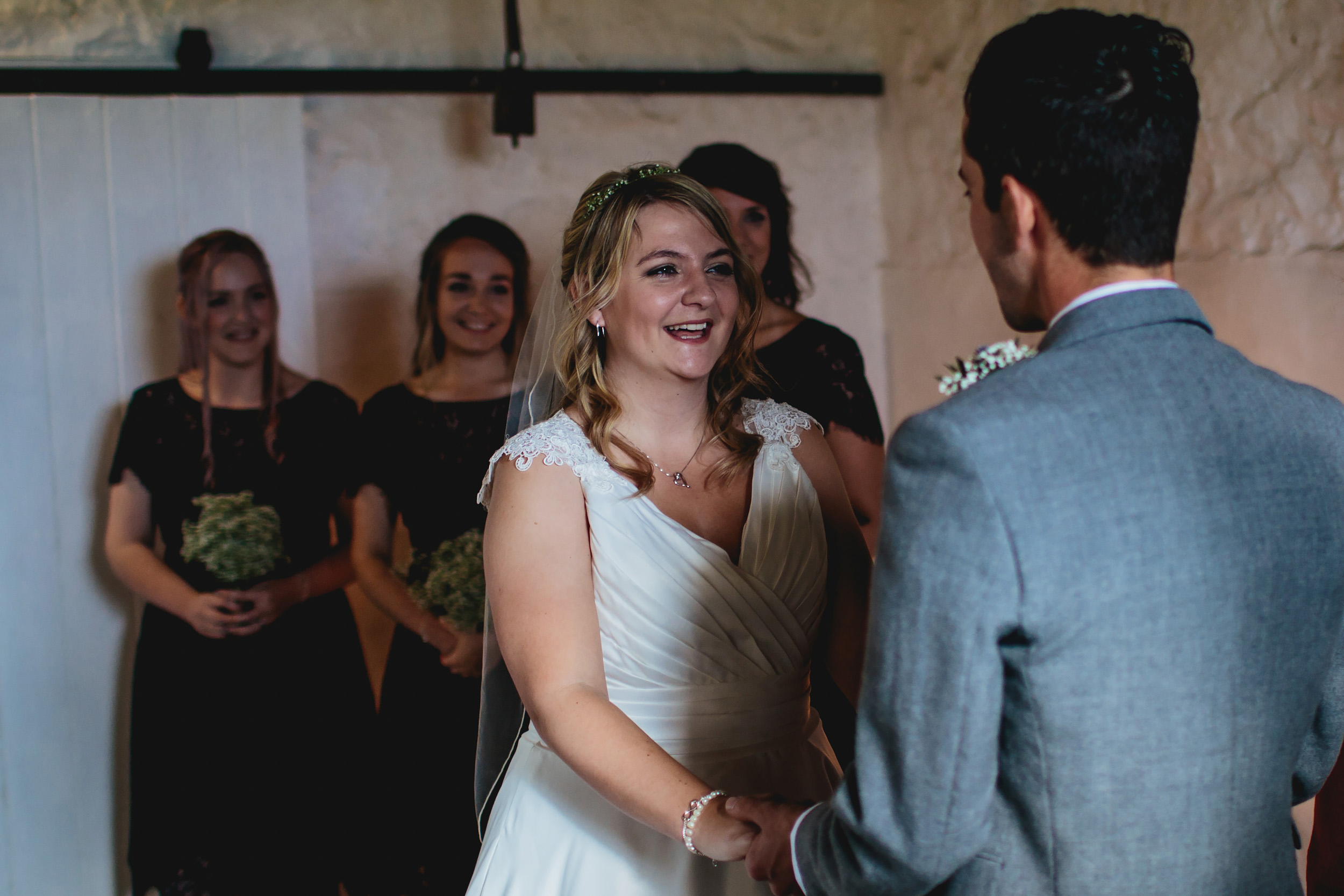 Bride smiling during the wedding ceremony at Cow Shed Crail