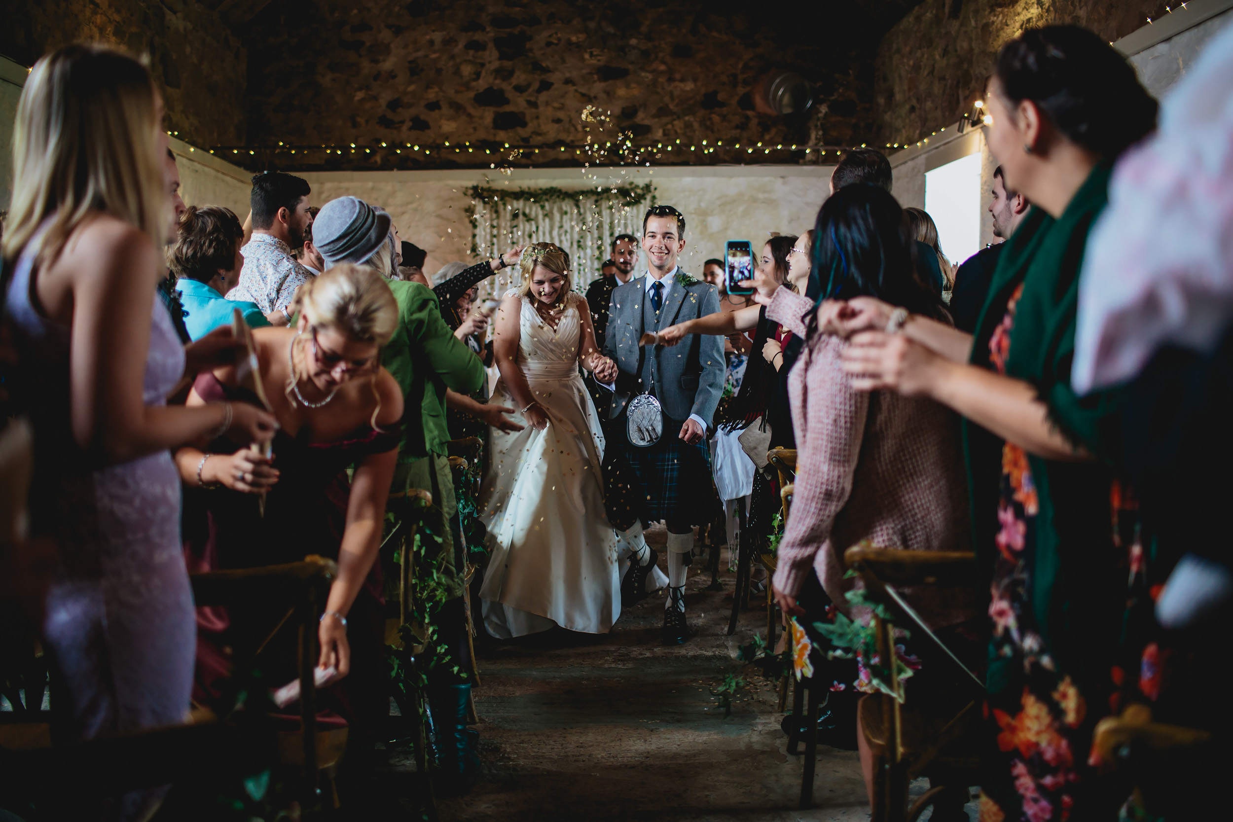 Bride and groom walk down the aisle at Cow Shed Crail