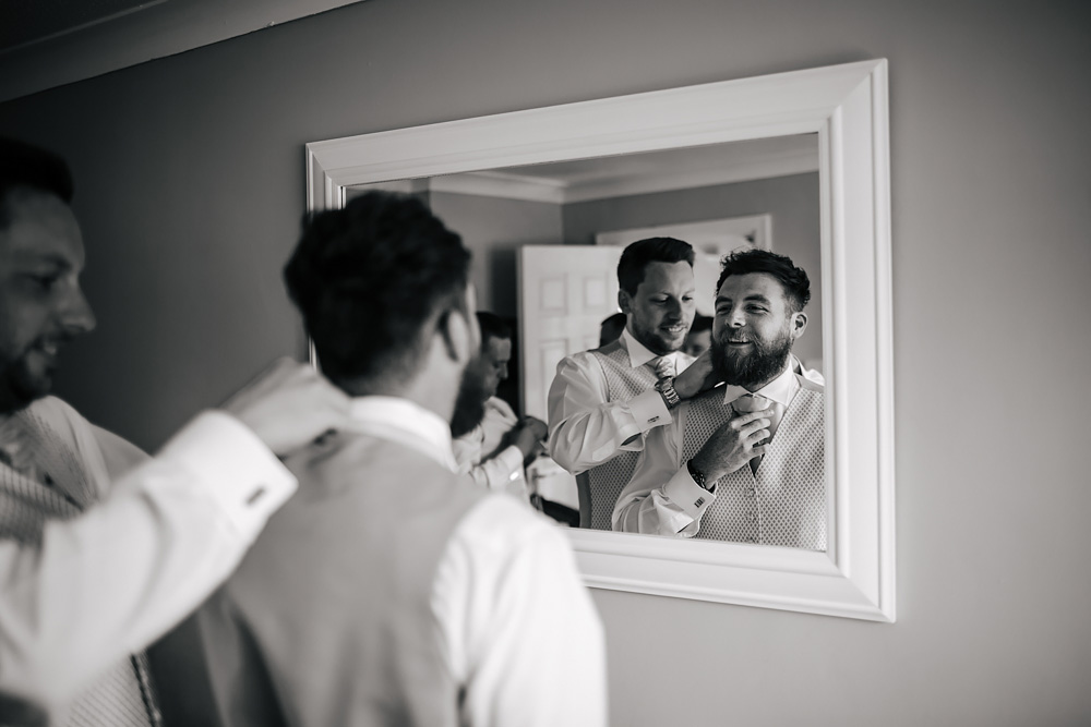 Groom prepares his tie in the mirror in Lancashire