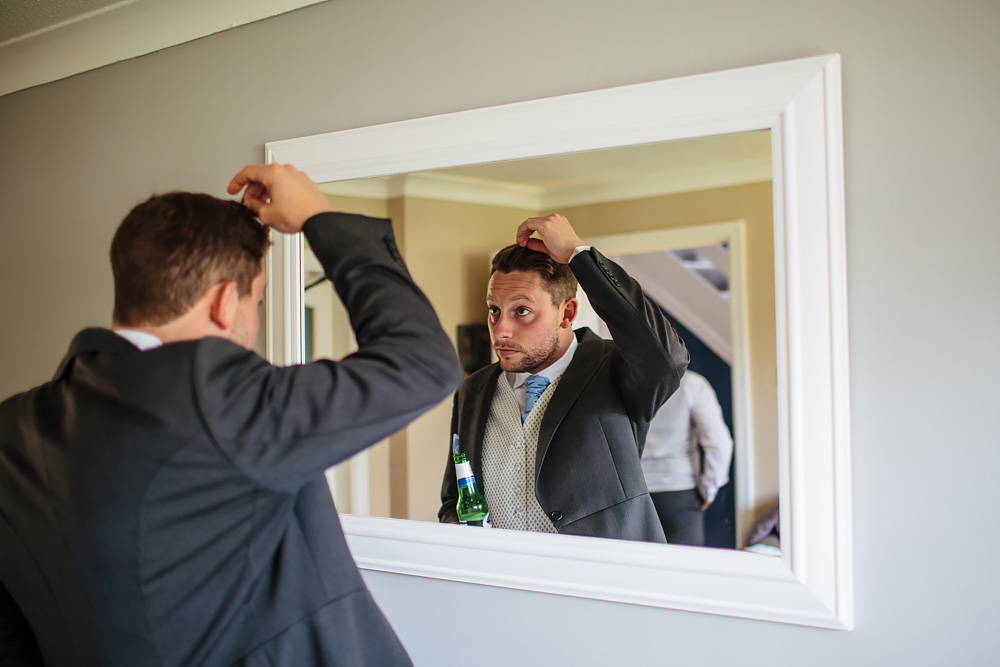 Best man does his hair in the mirror in Lancashire