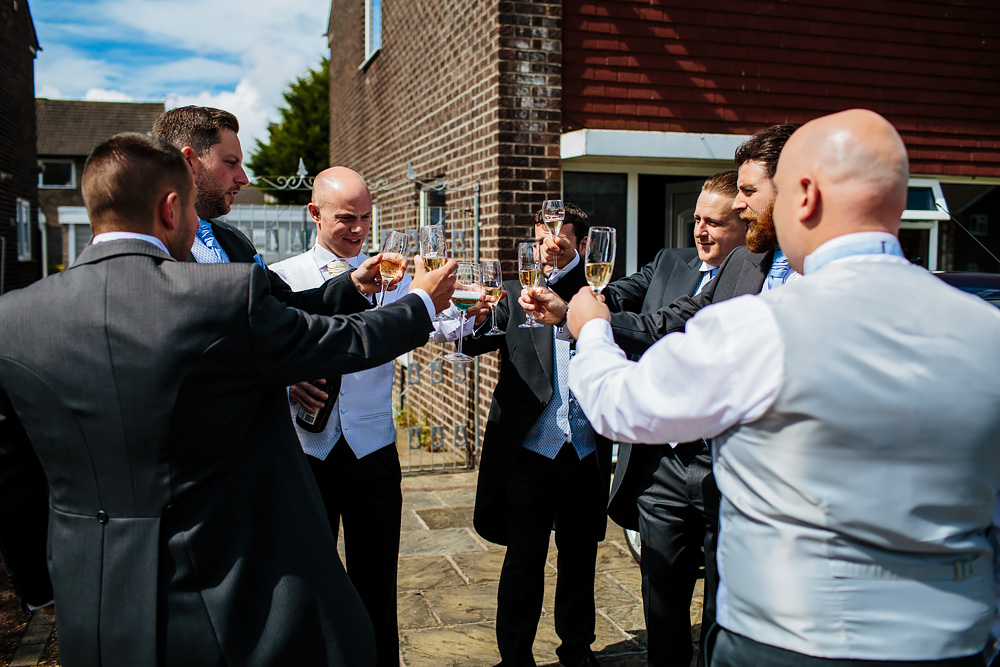 Groom and groomsmen drink champagne at a wedding