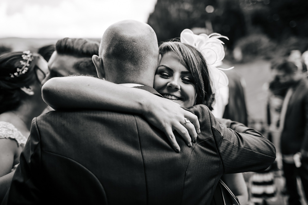 Groom and guests hugging at a wedding