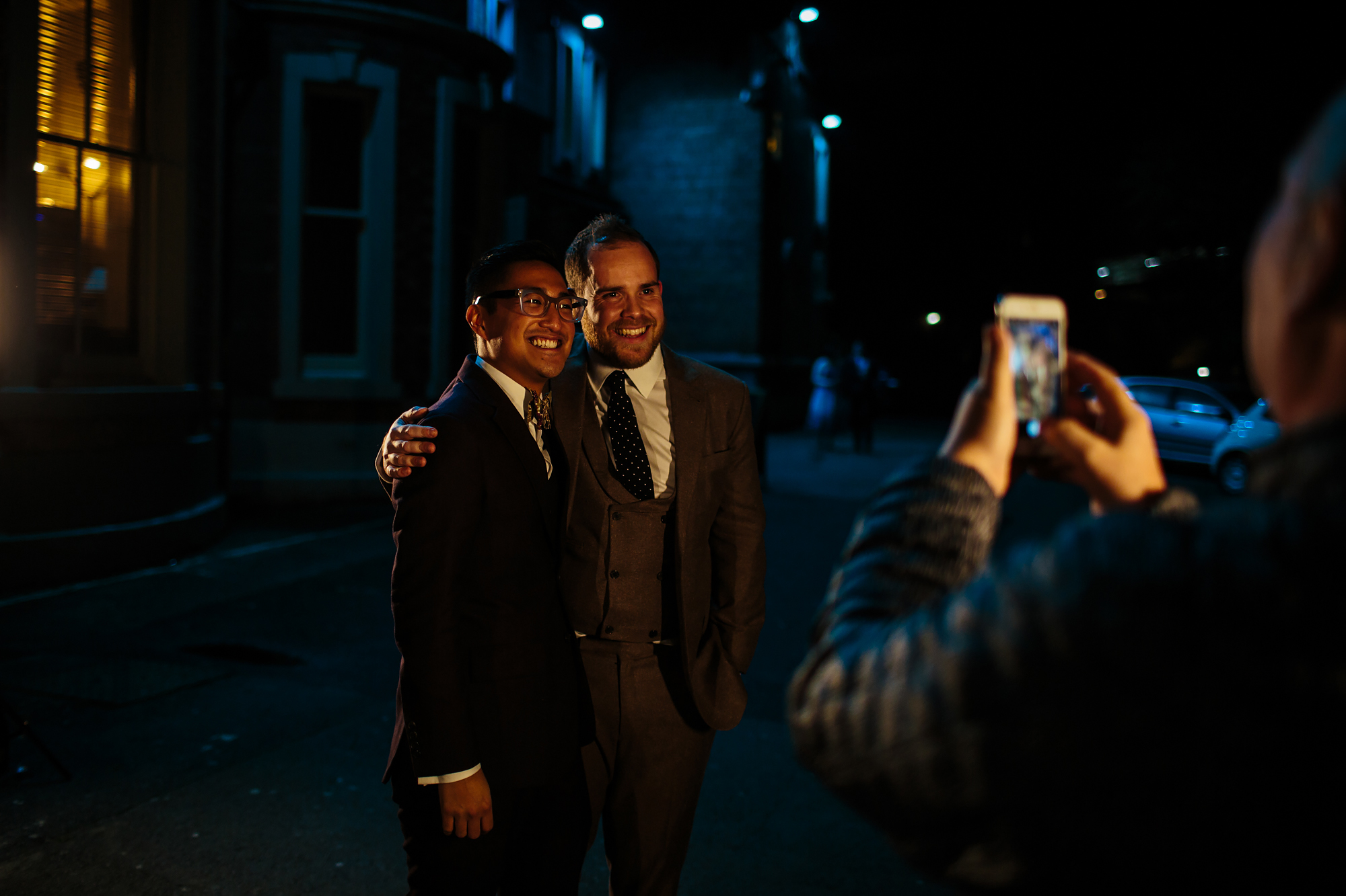 Grooms pose for a photo at a gay wedding