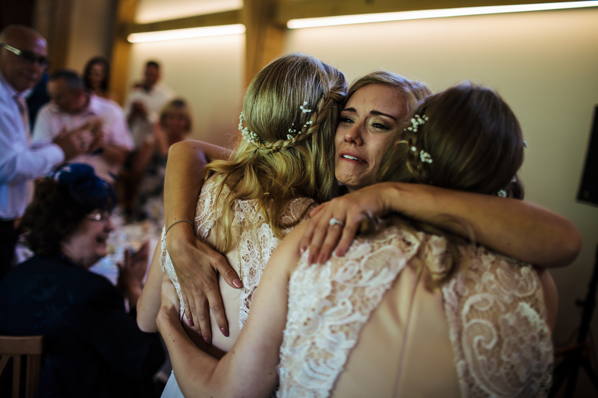 Bride hugging sisters at her emotional wedding