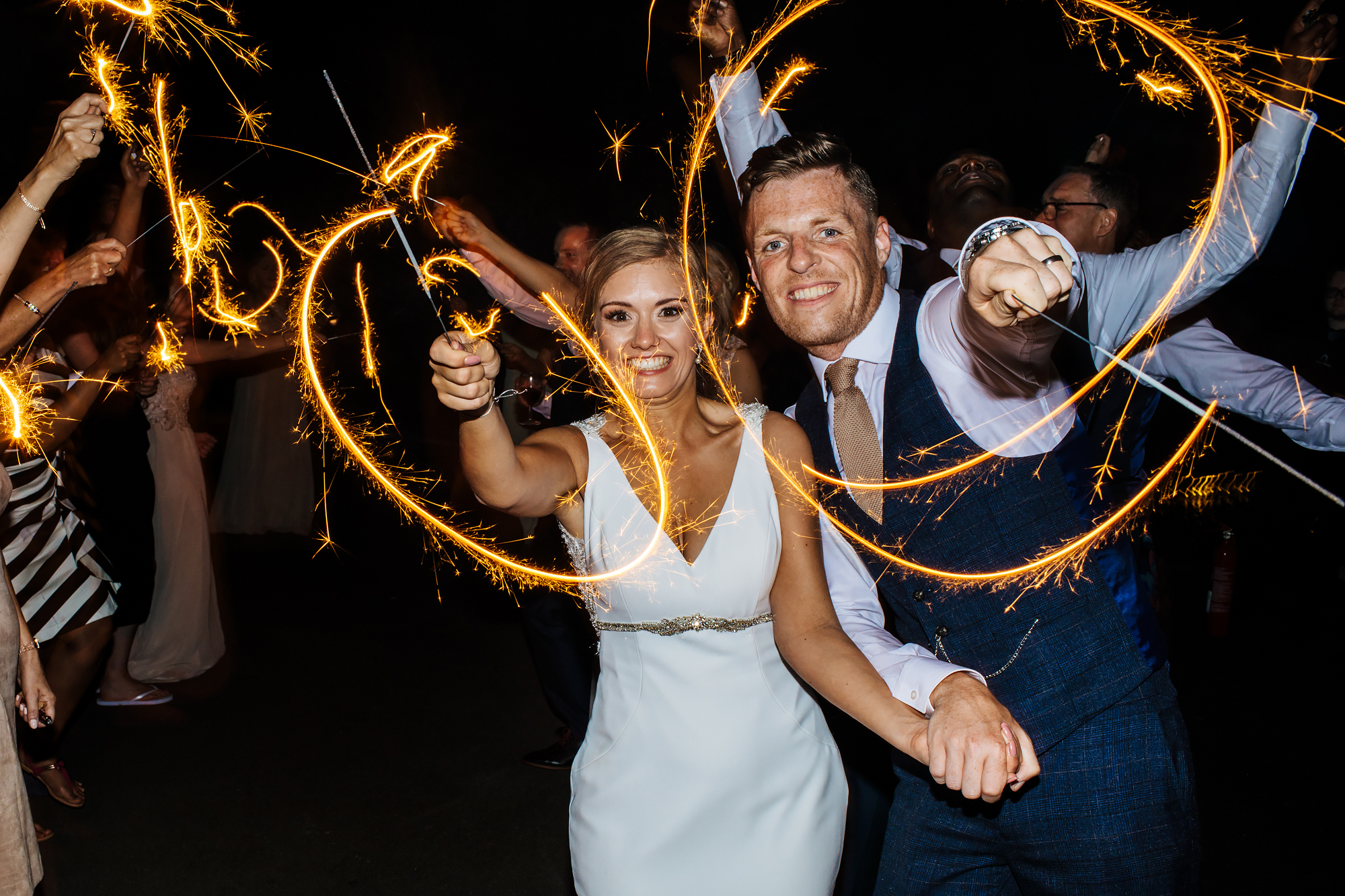 Bride and groom playing with sparklers at a wedding