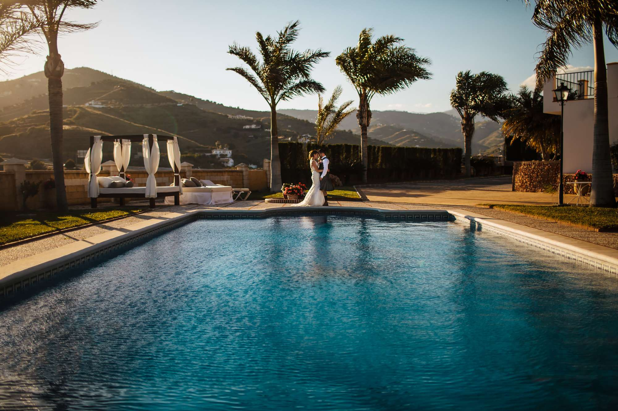Wedding portrait of couple by a swimming pool