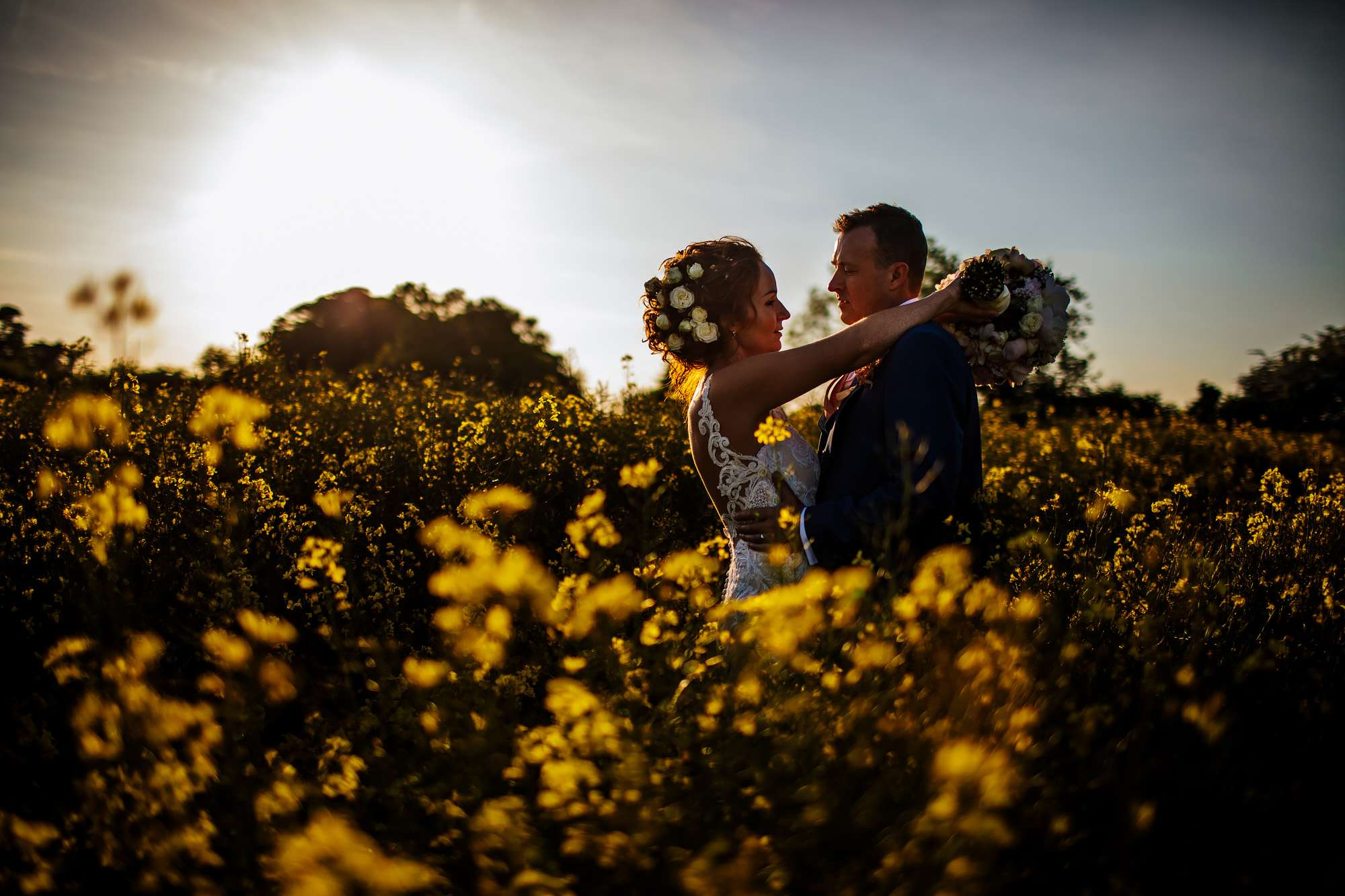 Rapeseed field at sunset with a bride and groom