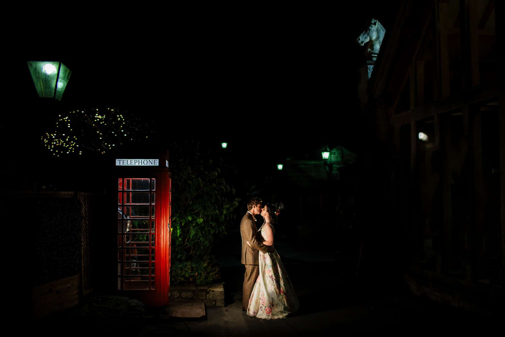 Bride and groom kissing by a red phone box at a Yorkshire Wedding