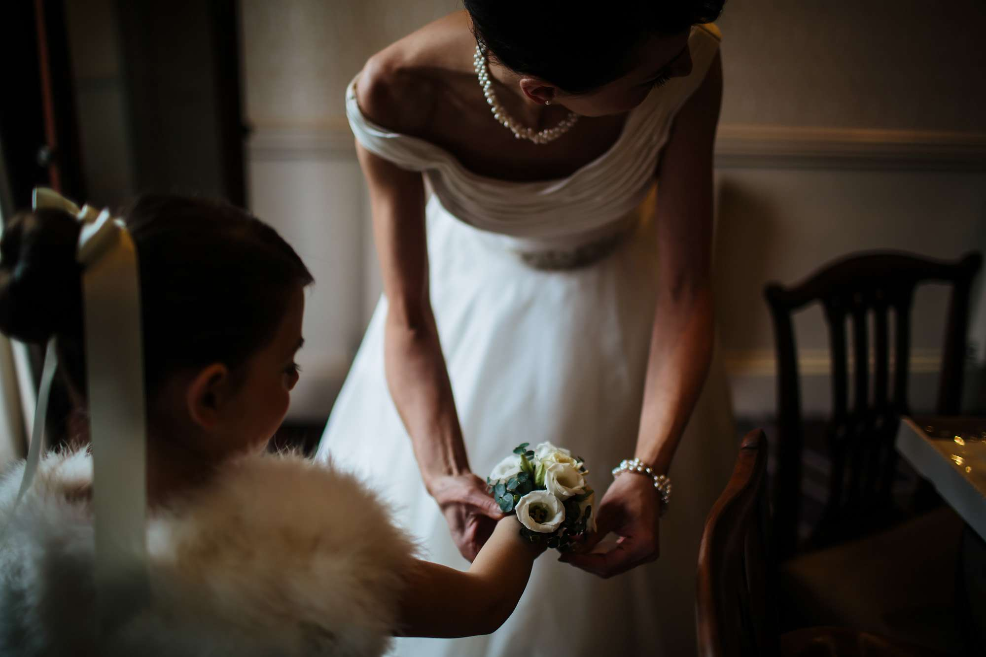 Bride attaches a flower bracelet to her daughter bridesmaid