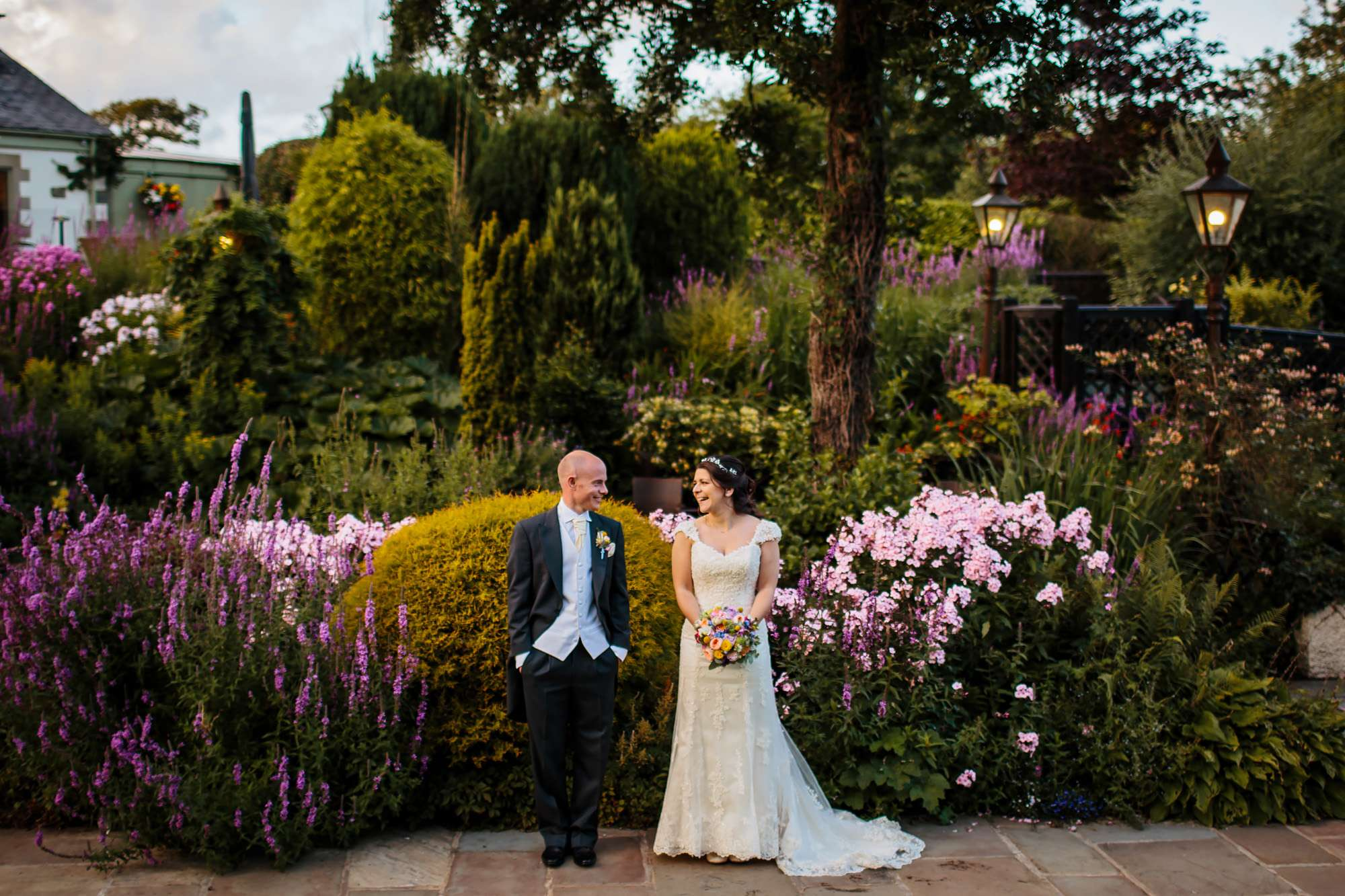 Bride and groom laughing in front of a flower bed in Yorkshire