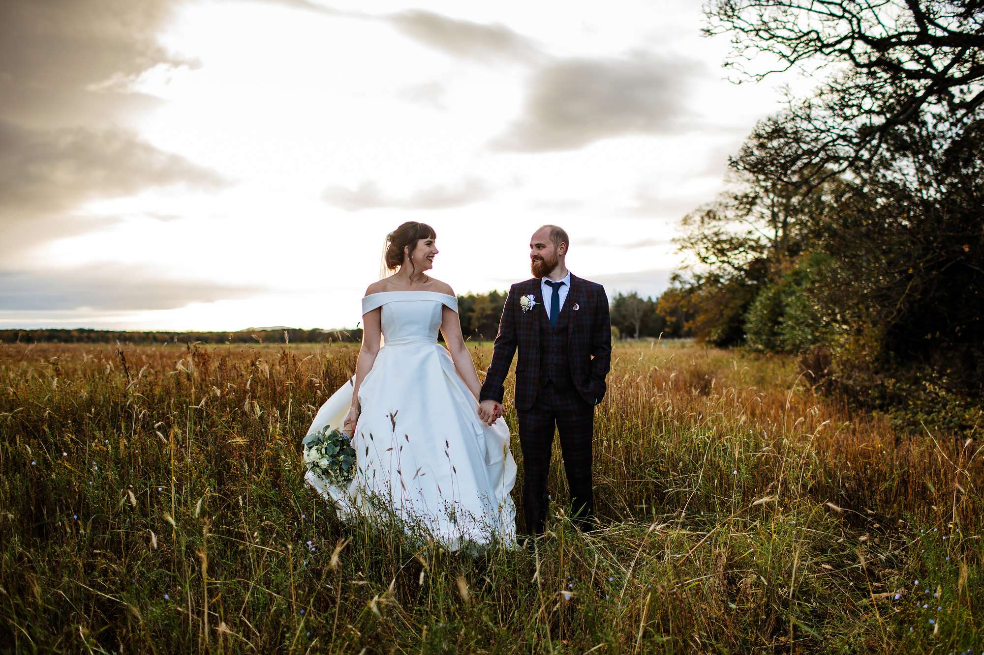 Bride and groom in a field at sunset in Leeds