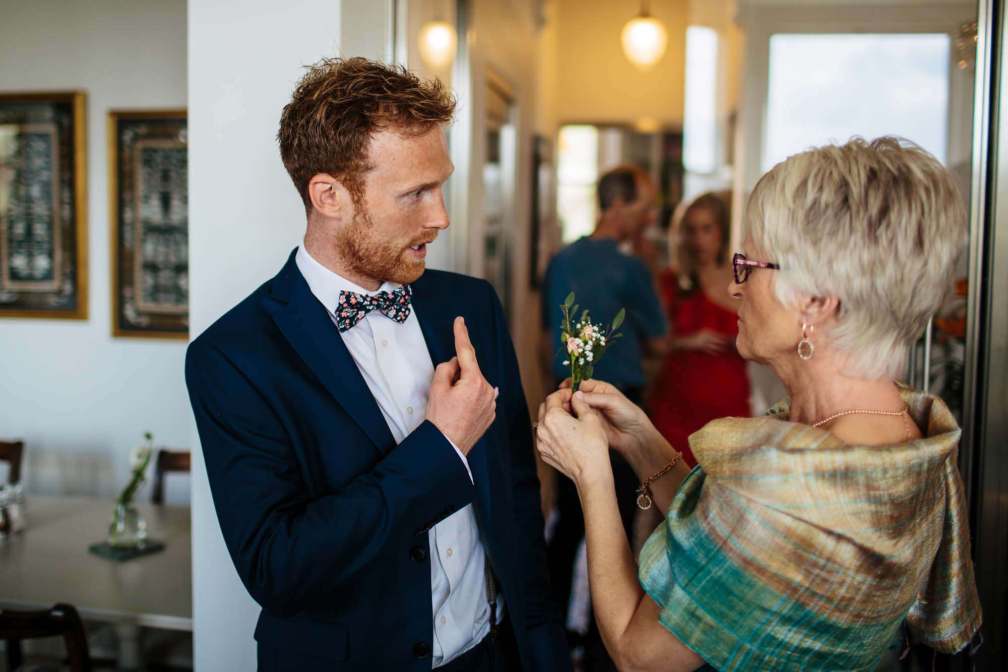 Grooms mum puts his buttonhole flower in