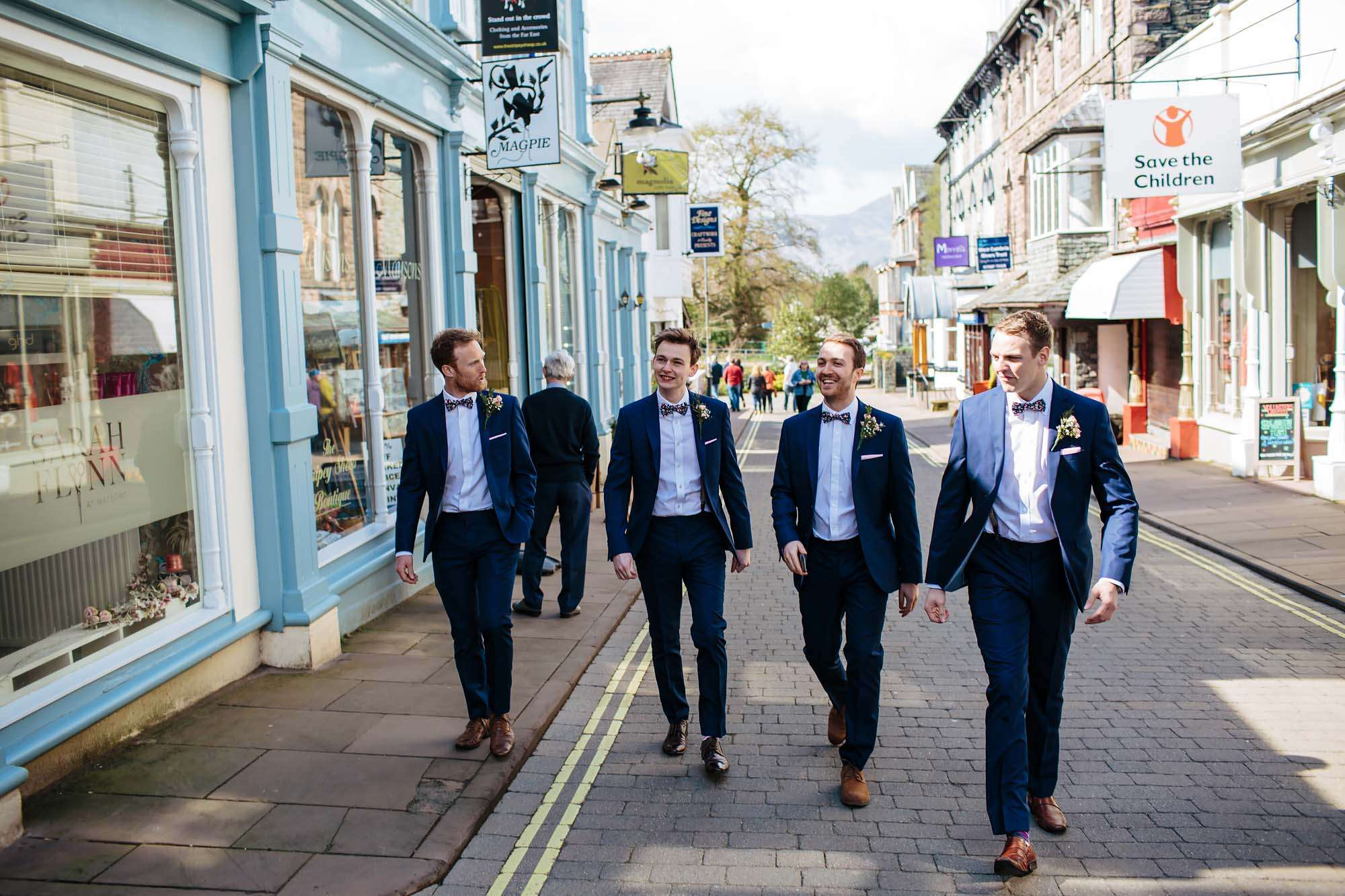 Groom and boys walking through Keswick town to the wedding