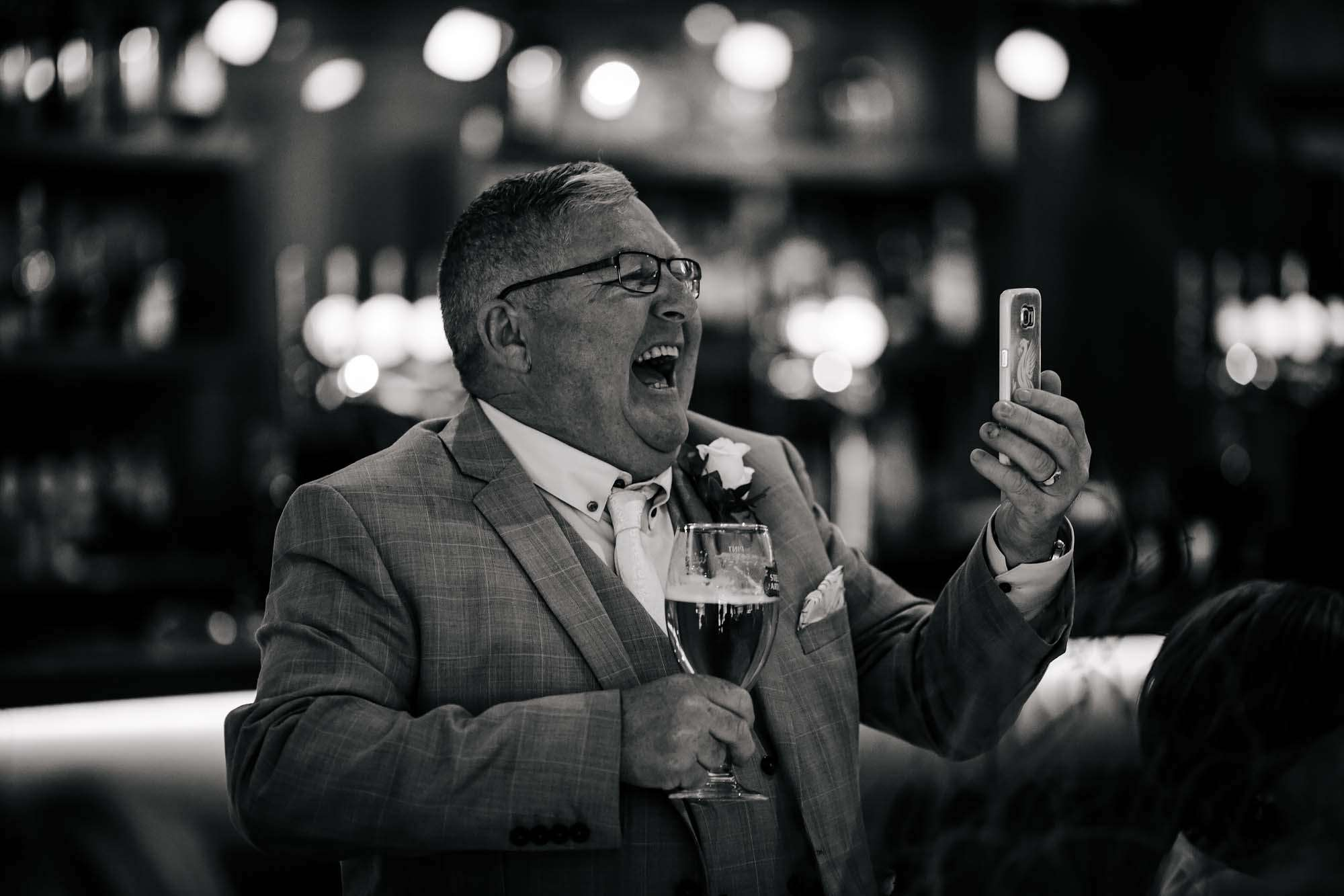 Wedding guest laughing at his mobile phone