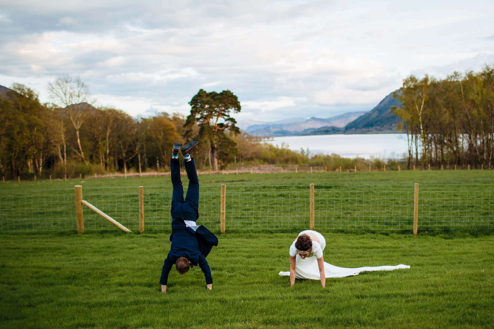 Bride and groom doing handstands at Lake Bassenthwaite