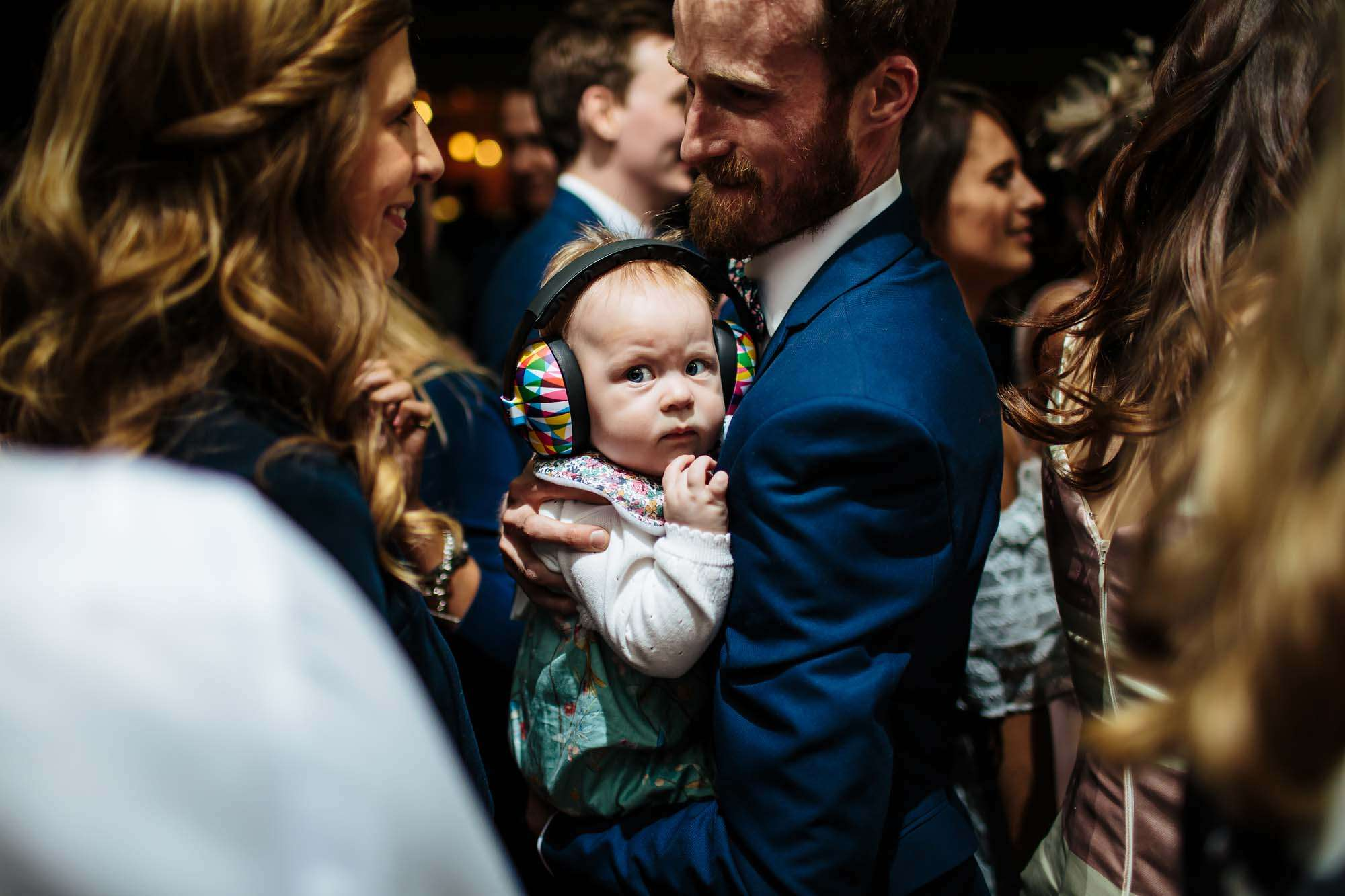 Young baby with ear defenders at a wedding