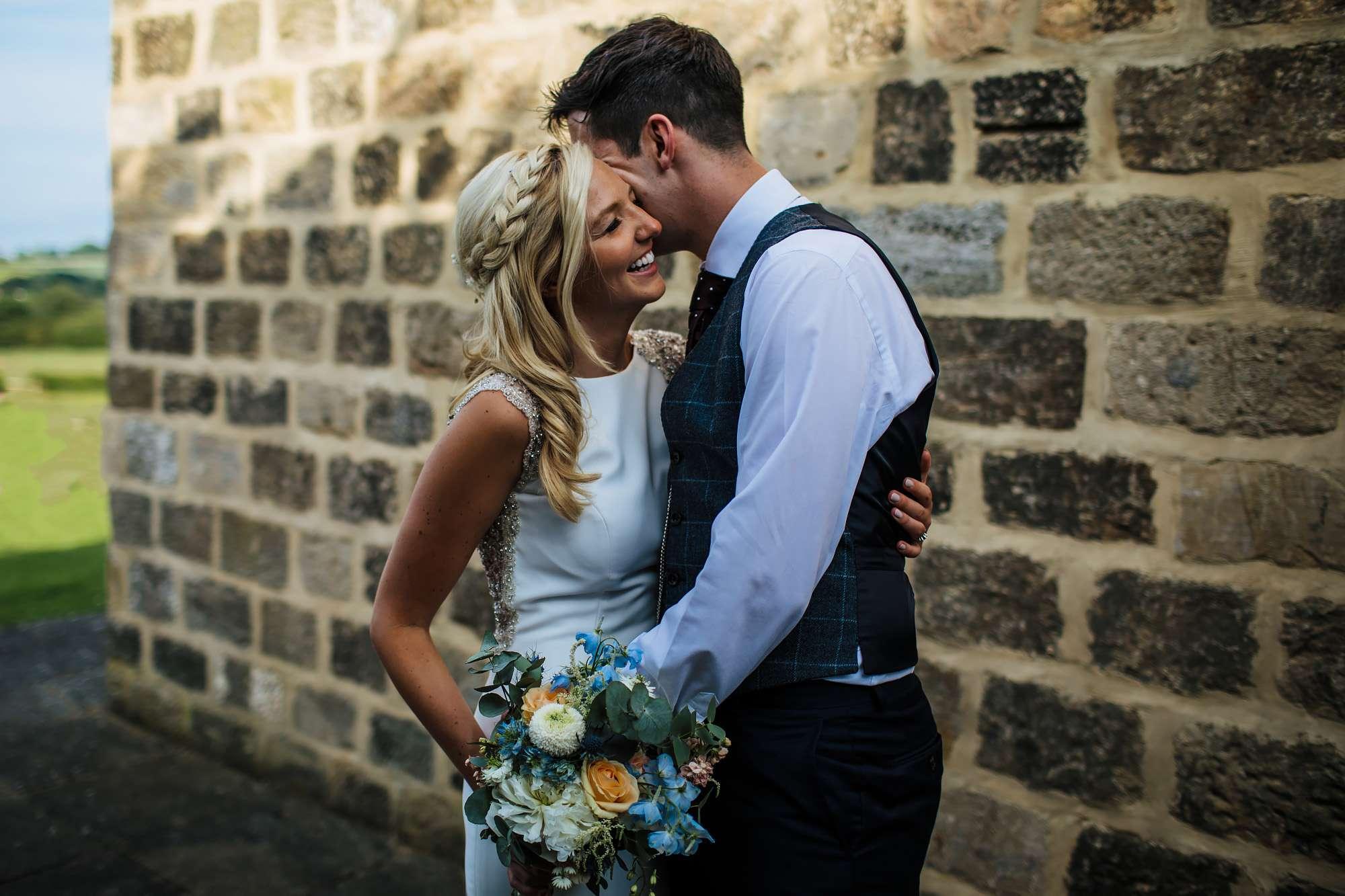 Bride and groom posing at East Keswick Village Hall