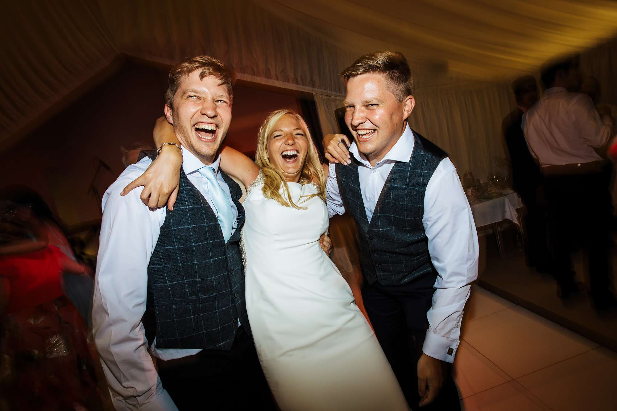 Bride and her brothers laughing at her wedding
