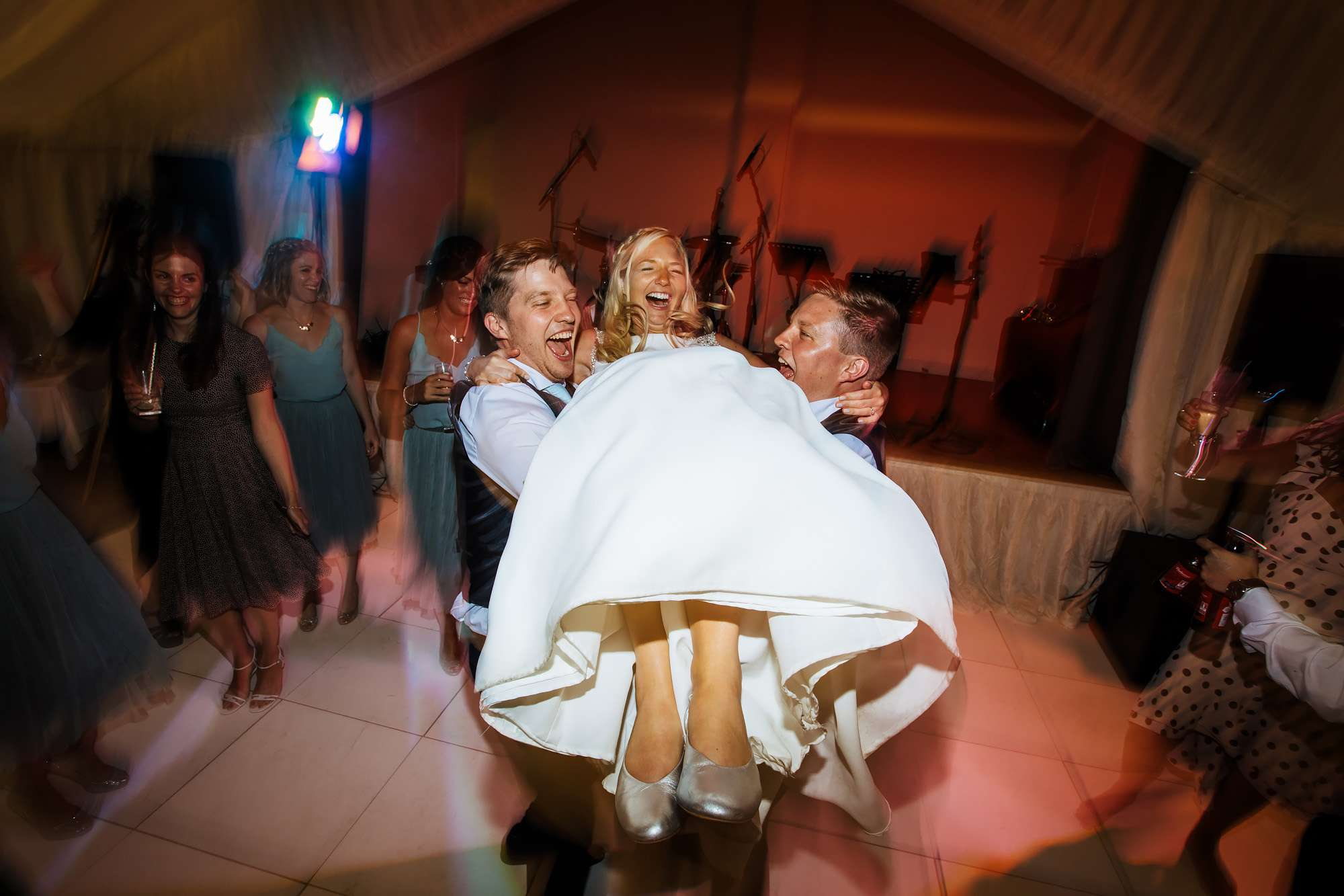 Bride being lifted on the dance floor at East Keswick Village Hall