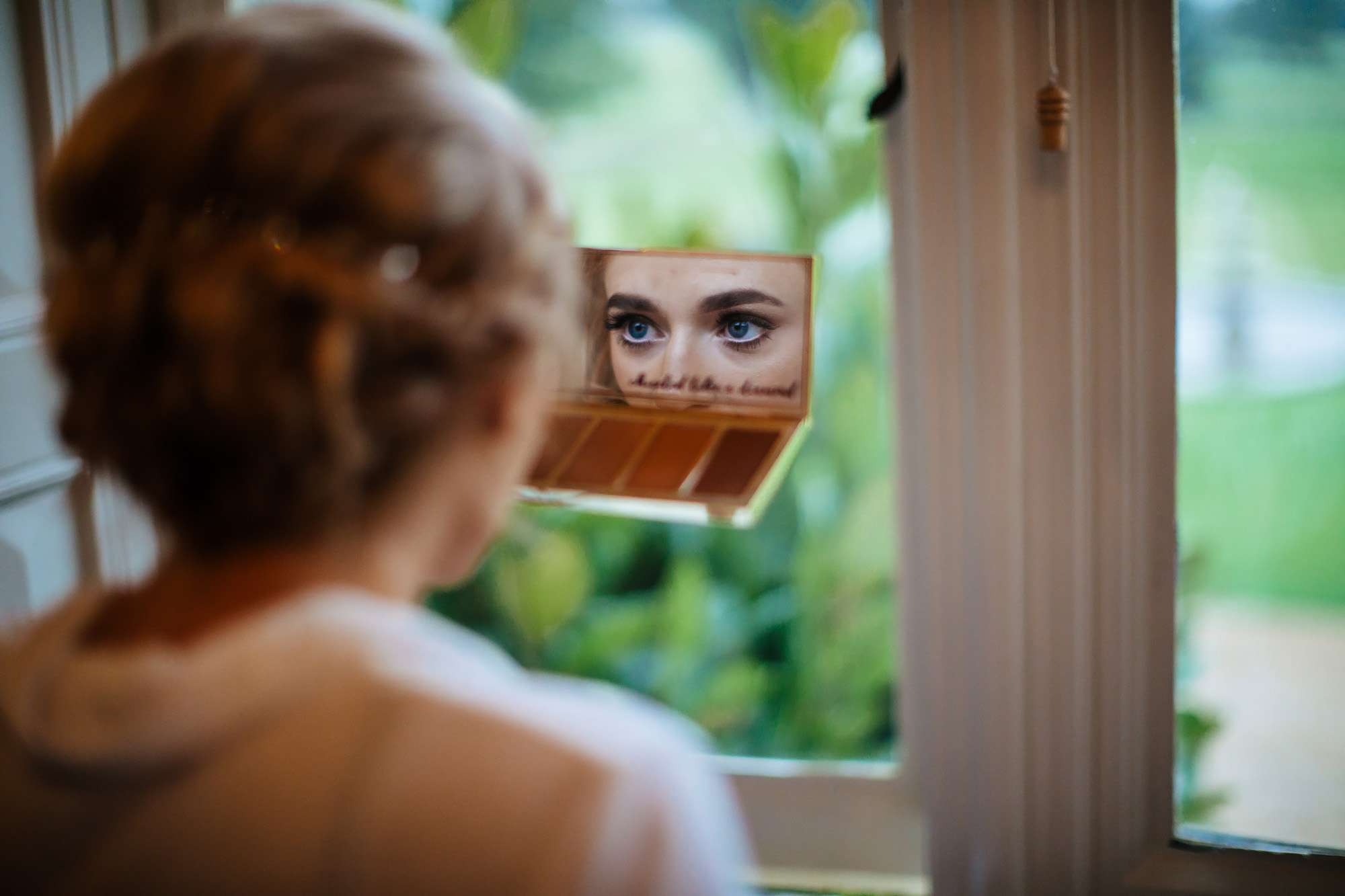 Bride looking in a make up mirror at her wedding