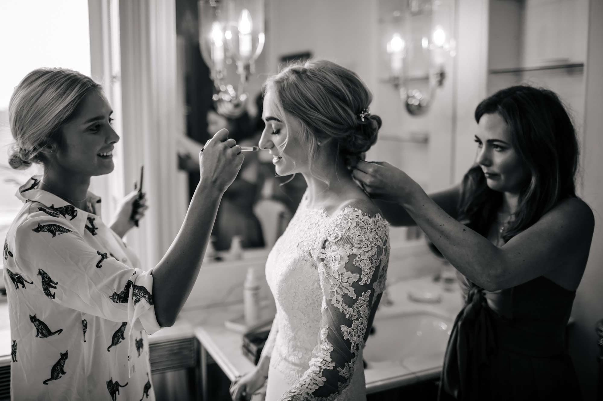 Wedding guests helping the bride get ready at her wedding
