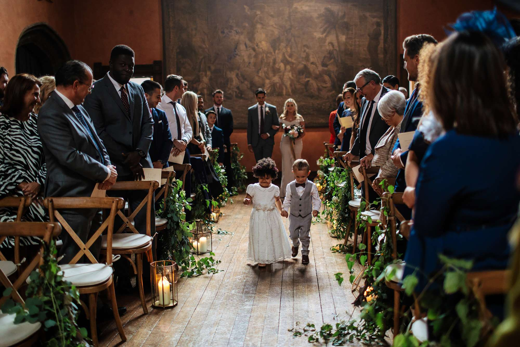 Young children walk down the aisle at a wedding at Cowdray House