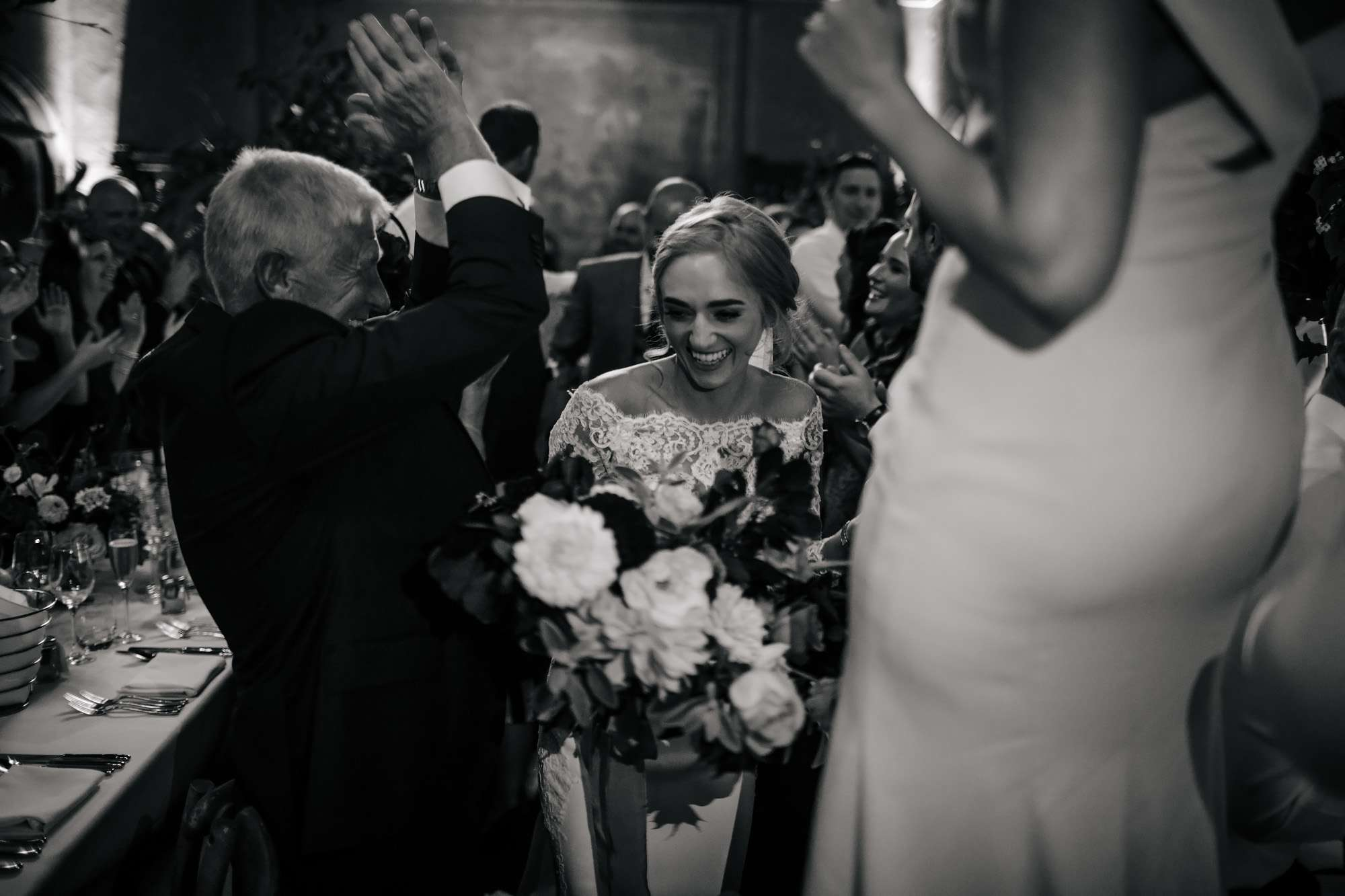 Guests cheer as bride and groom enter the dining room
