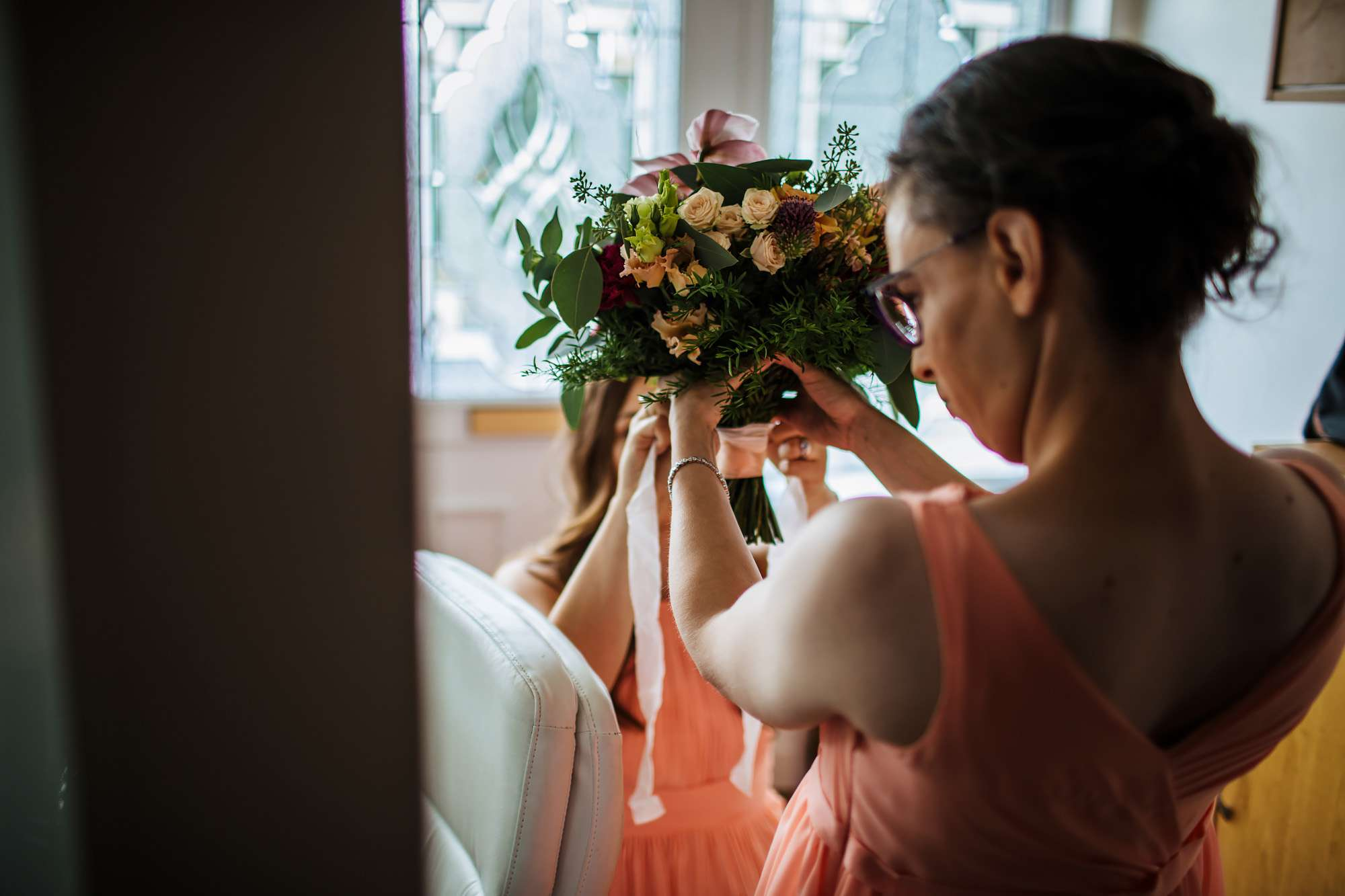 Bridesmaid holding the bride's bouquet at a wedding