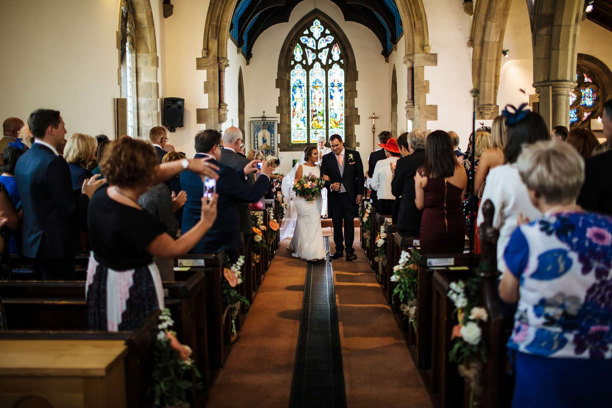 Newlyweds walking down the church aisle in Huddersfield