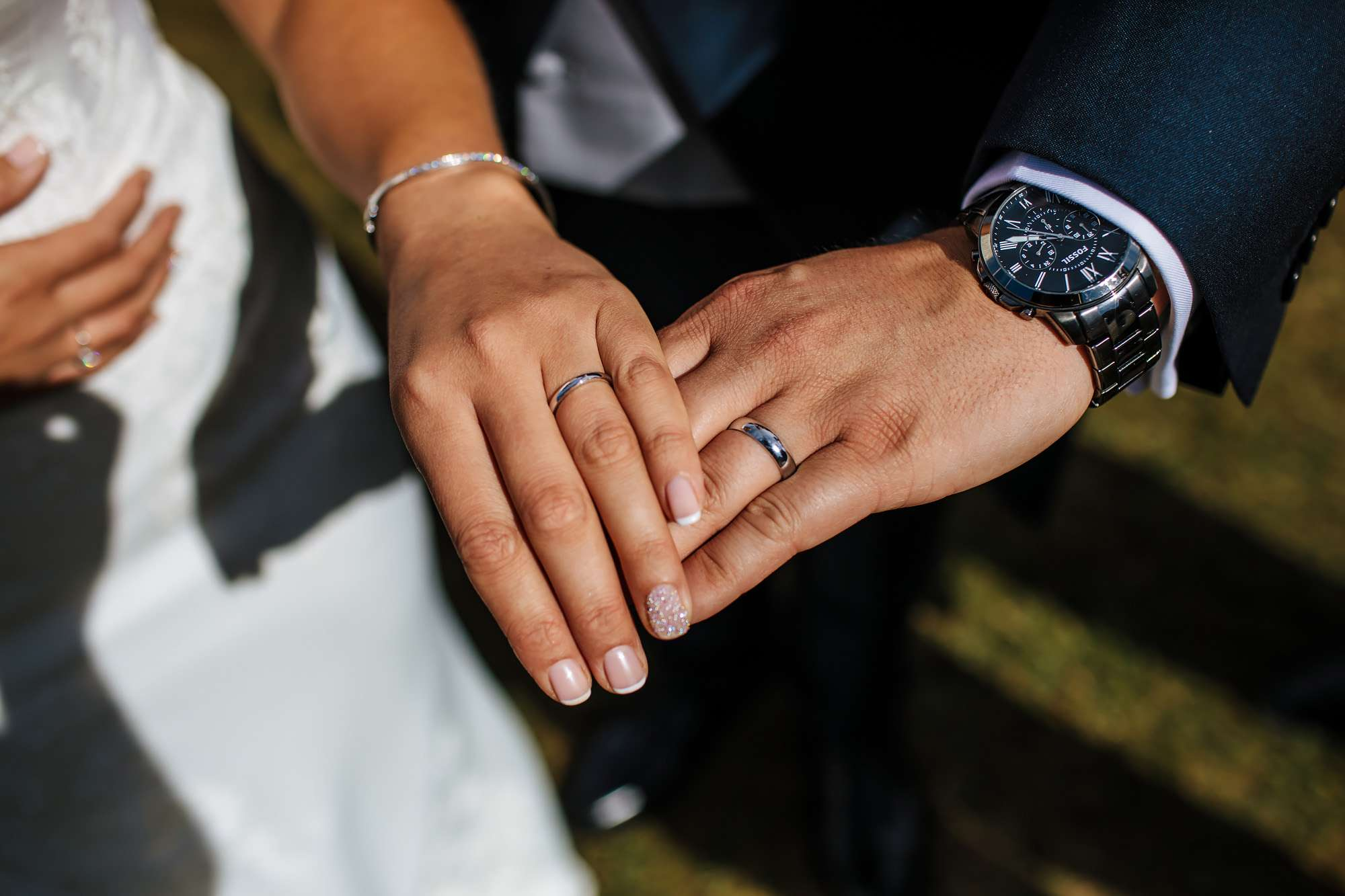 Bride and groom showing off their wedding rings