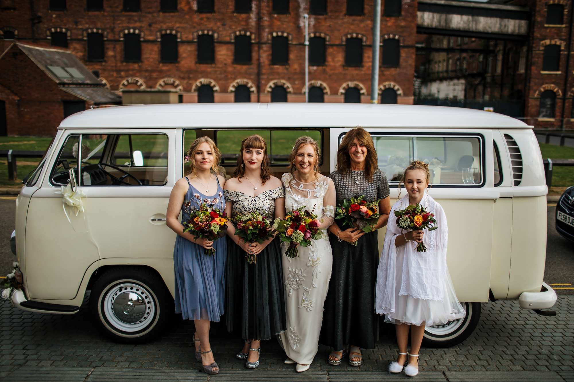 Bridal party posing in front of a VW campervan