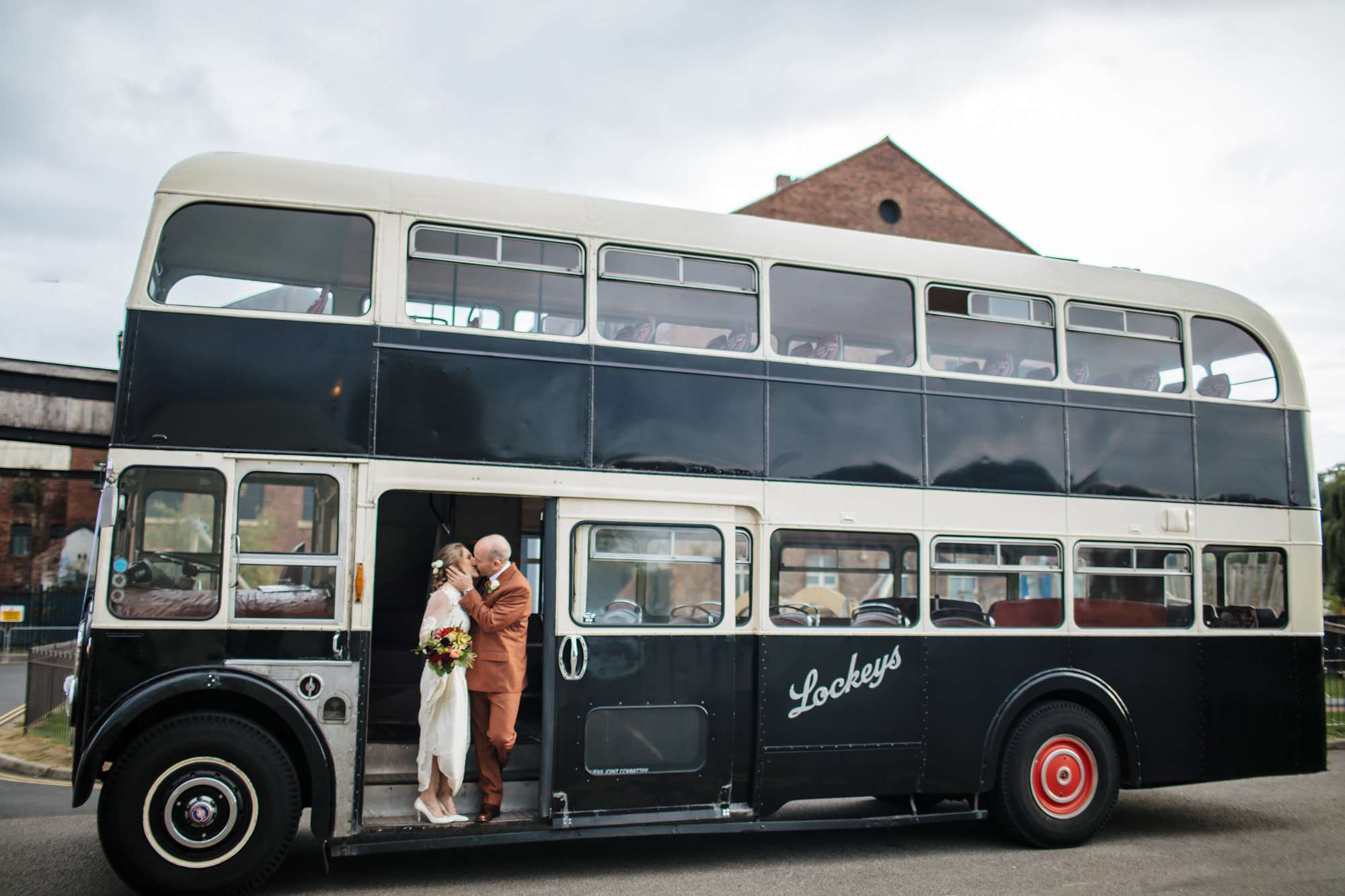 Bride and groom kissing on a vintage bus in Wakefield