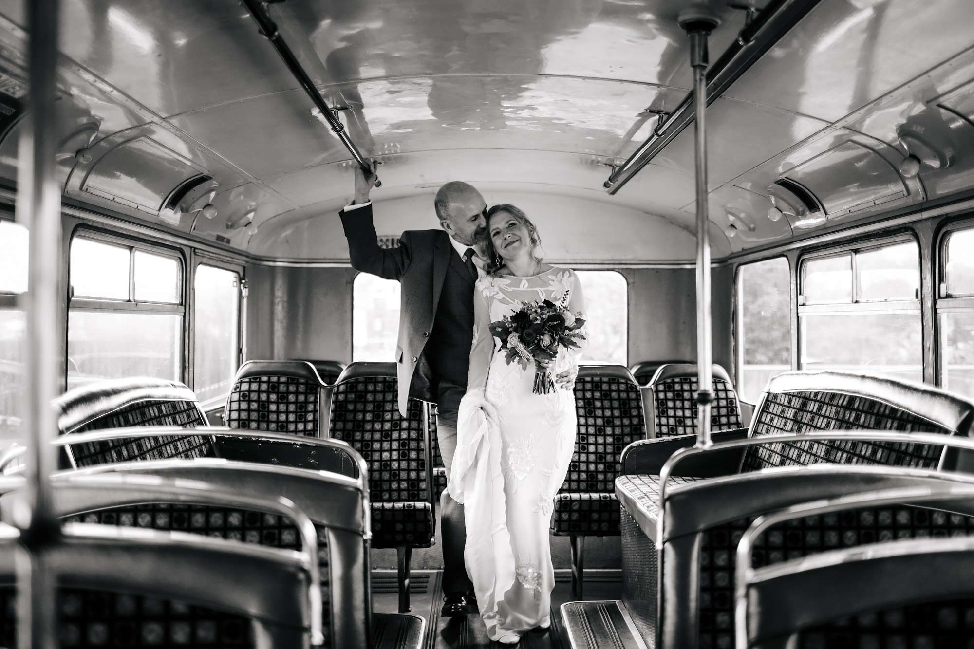Bride and groom posing on the bus at their wedding
