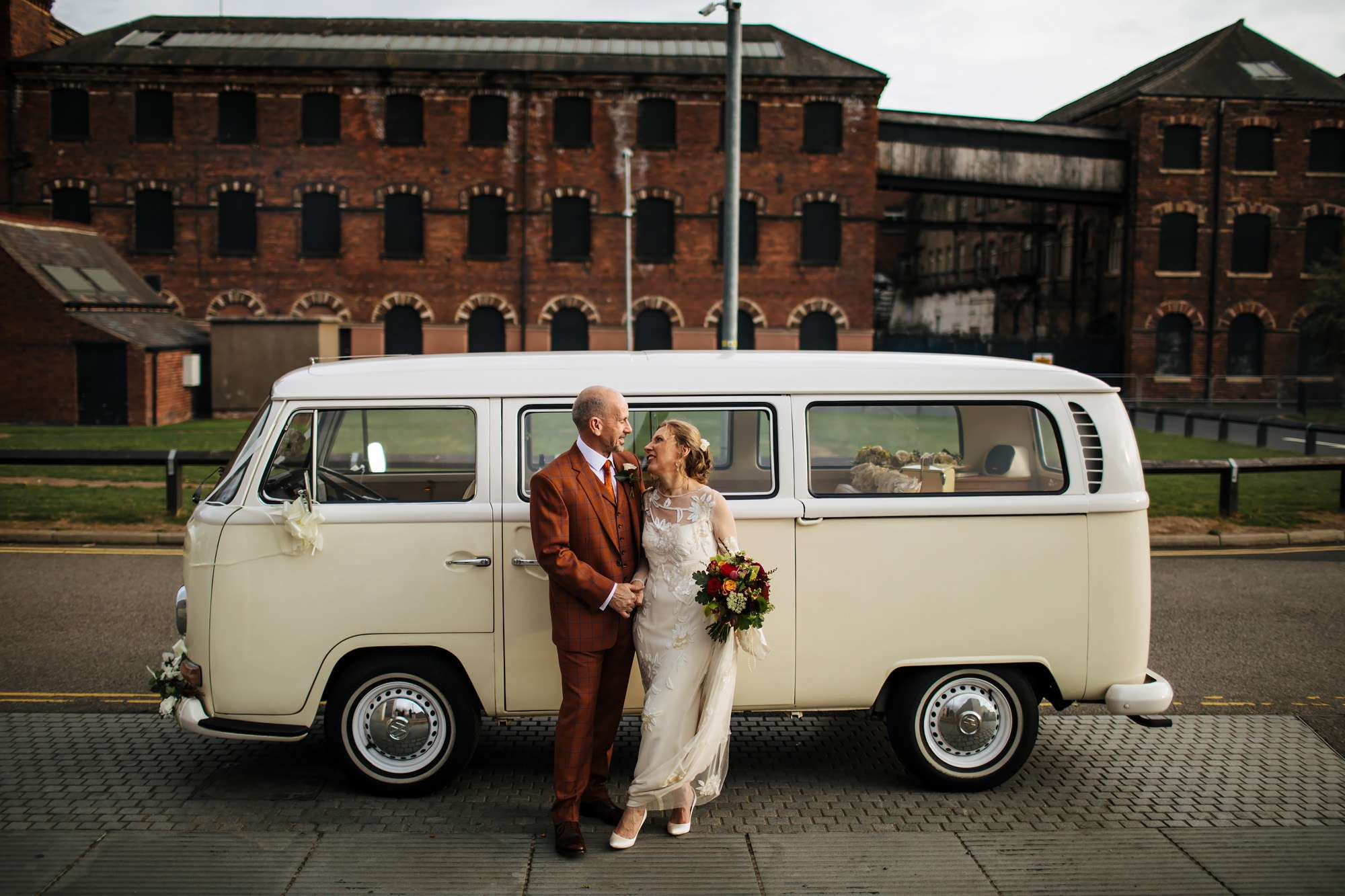 Bride and groom holding hands in front of a VW campervan