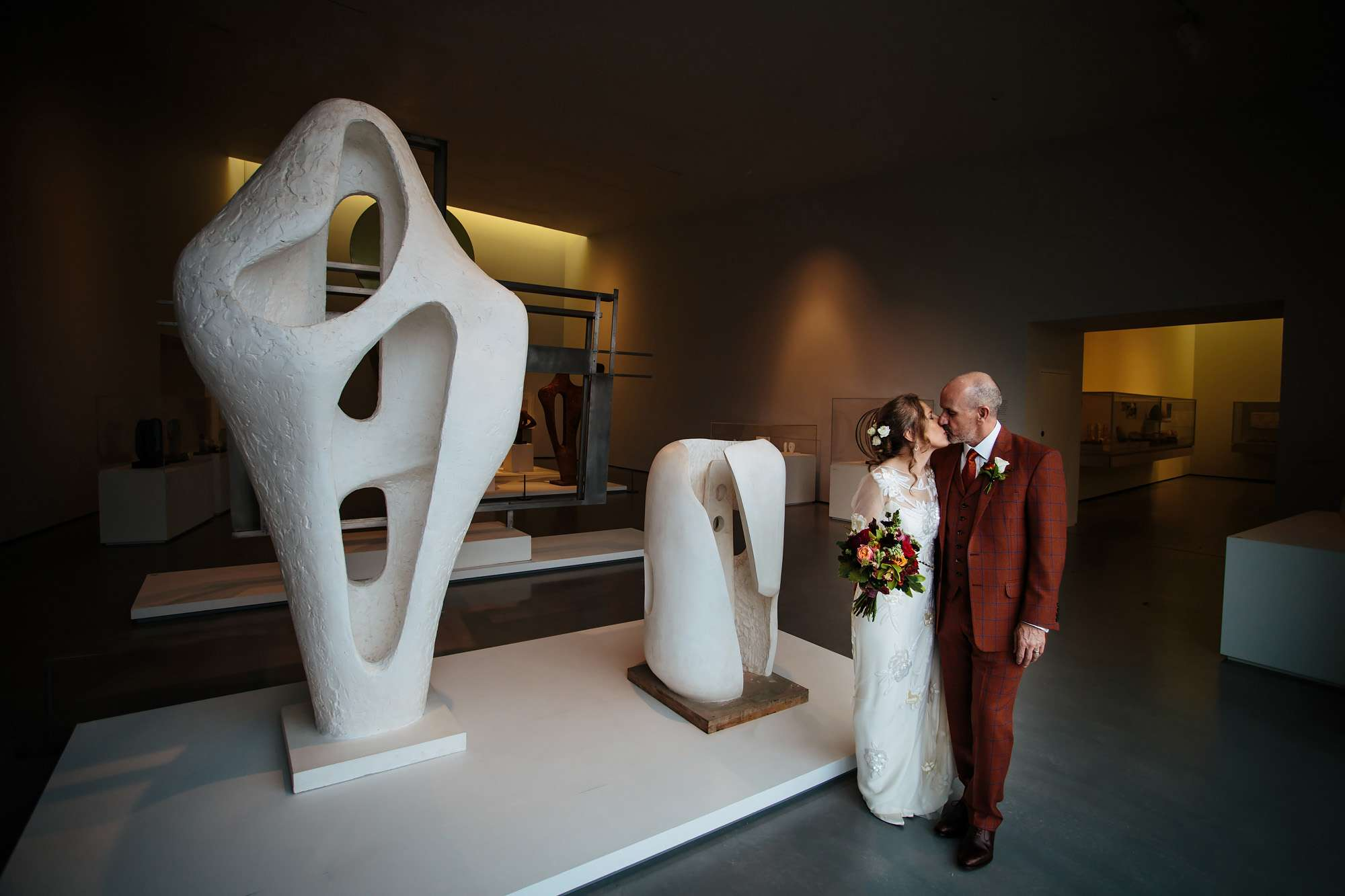Bride and groom kissing amongst the sculptures at Hepworth Art Gallery