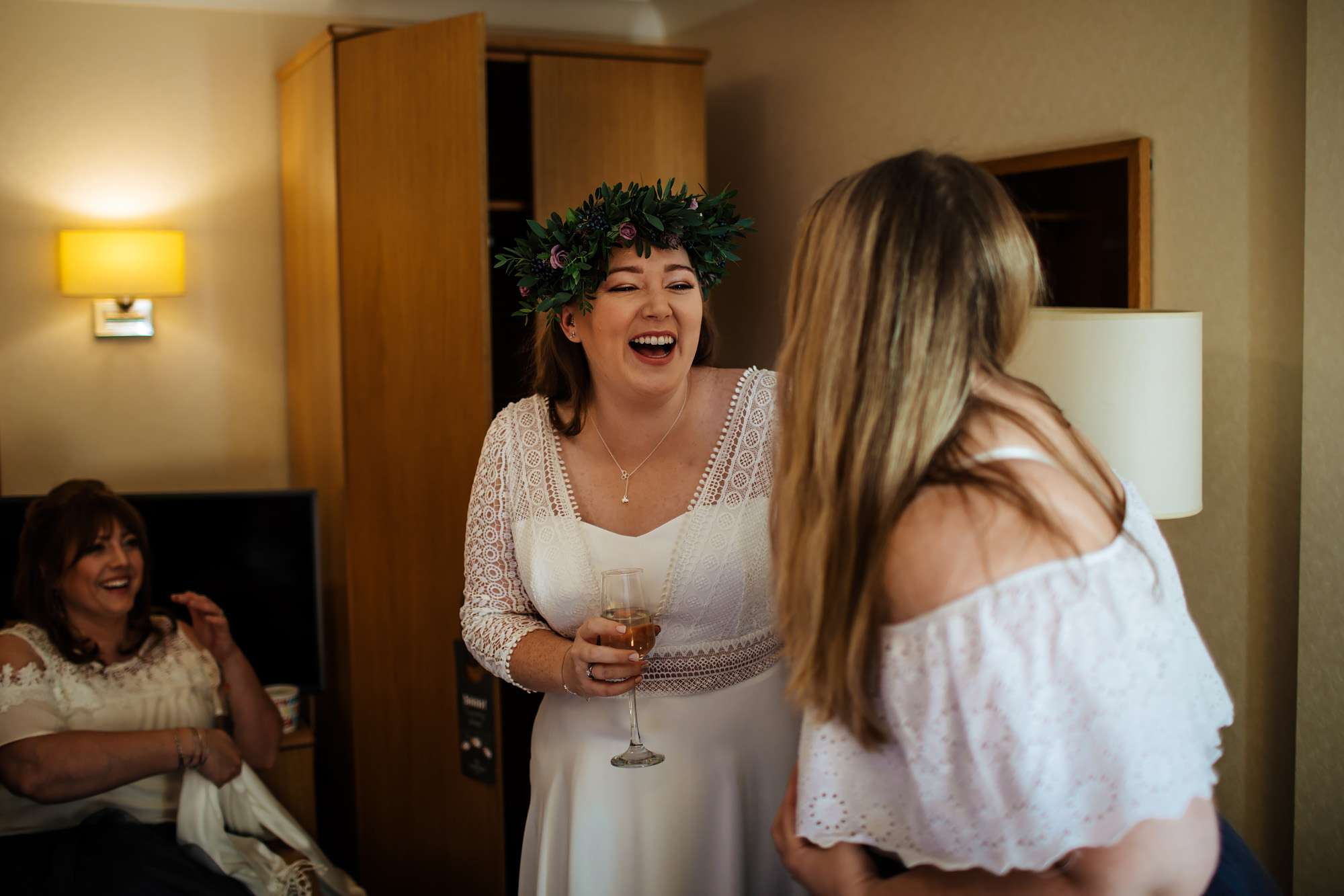 Bride laughing with her bridesmaid before her wedding
