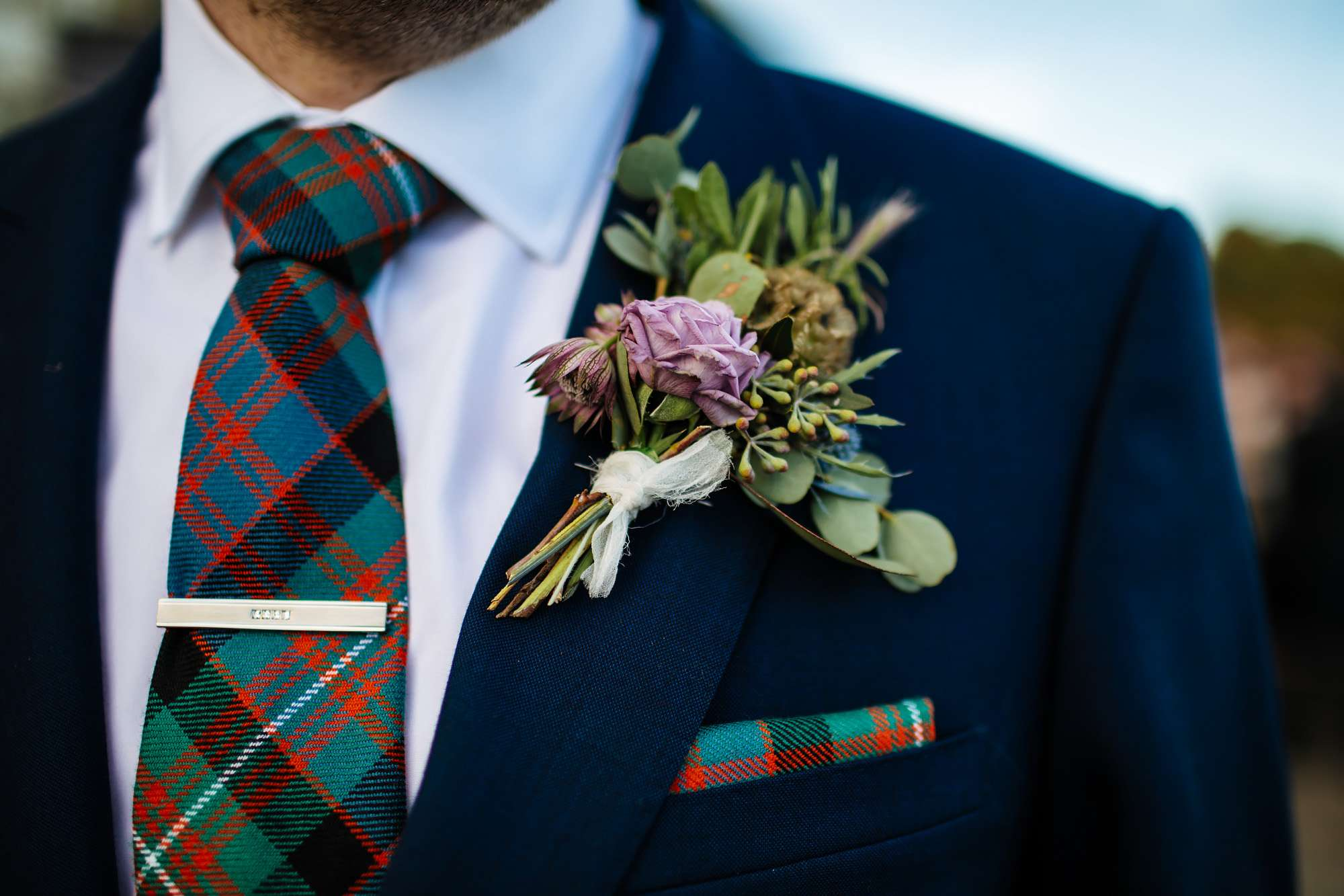 Close up of the groom's tartan tie and buttonhole