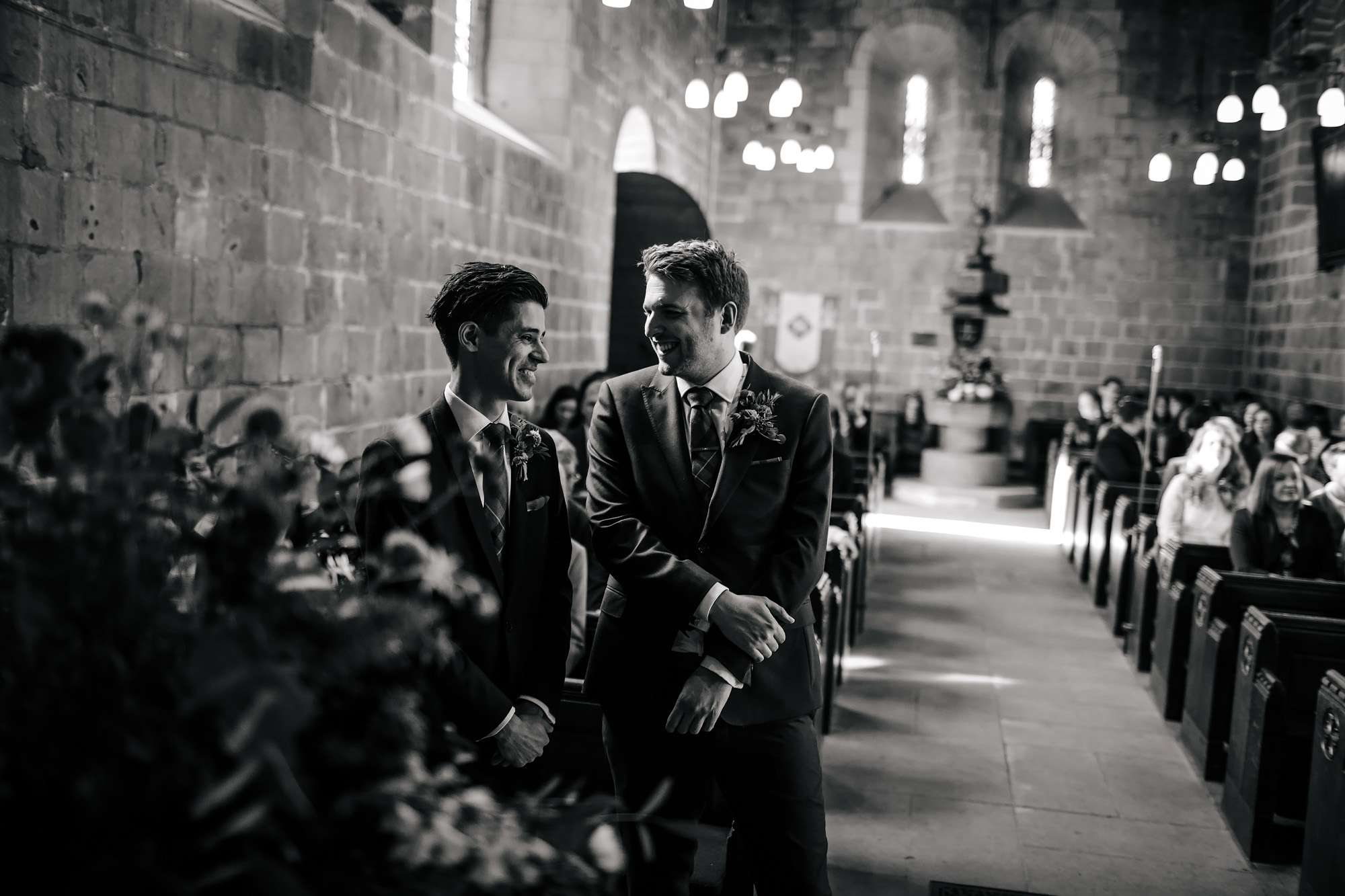 Groom and best man joking in the church